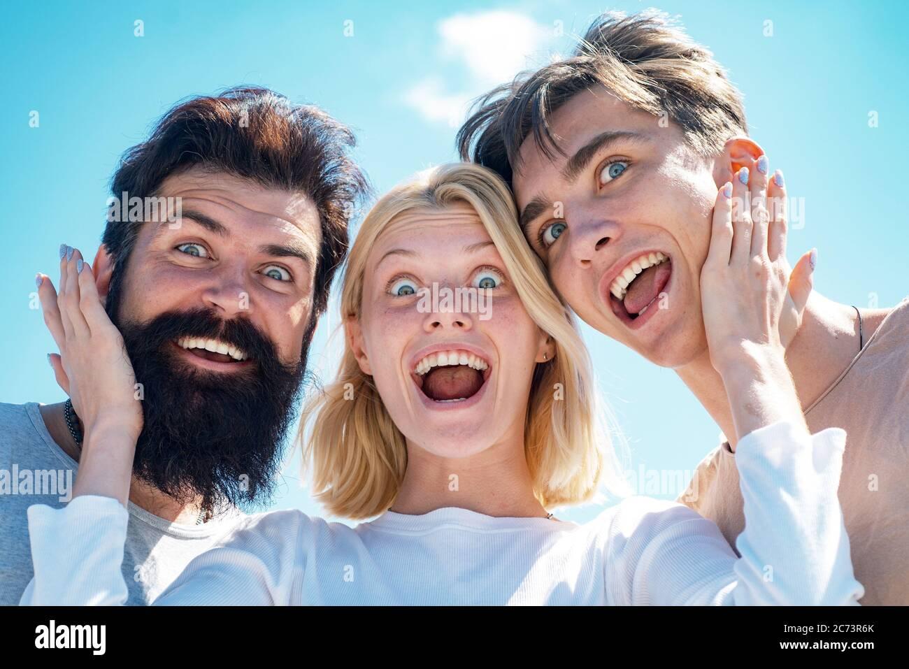 Jeunes de groupe enthousiastes - face à face. Compagnie de jeunes gens drôle à ciel ouvert. Deux garçons et une fille blonde regardant la caméra et ont Banque D'Images