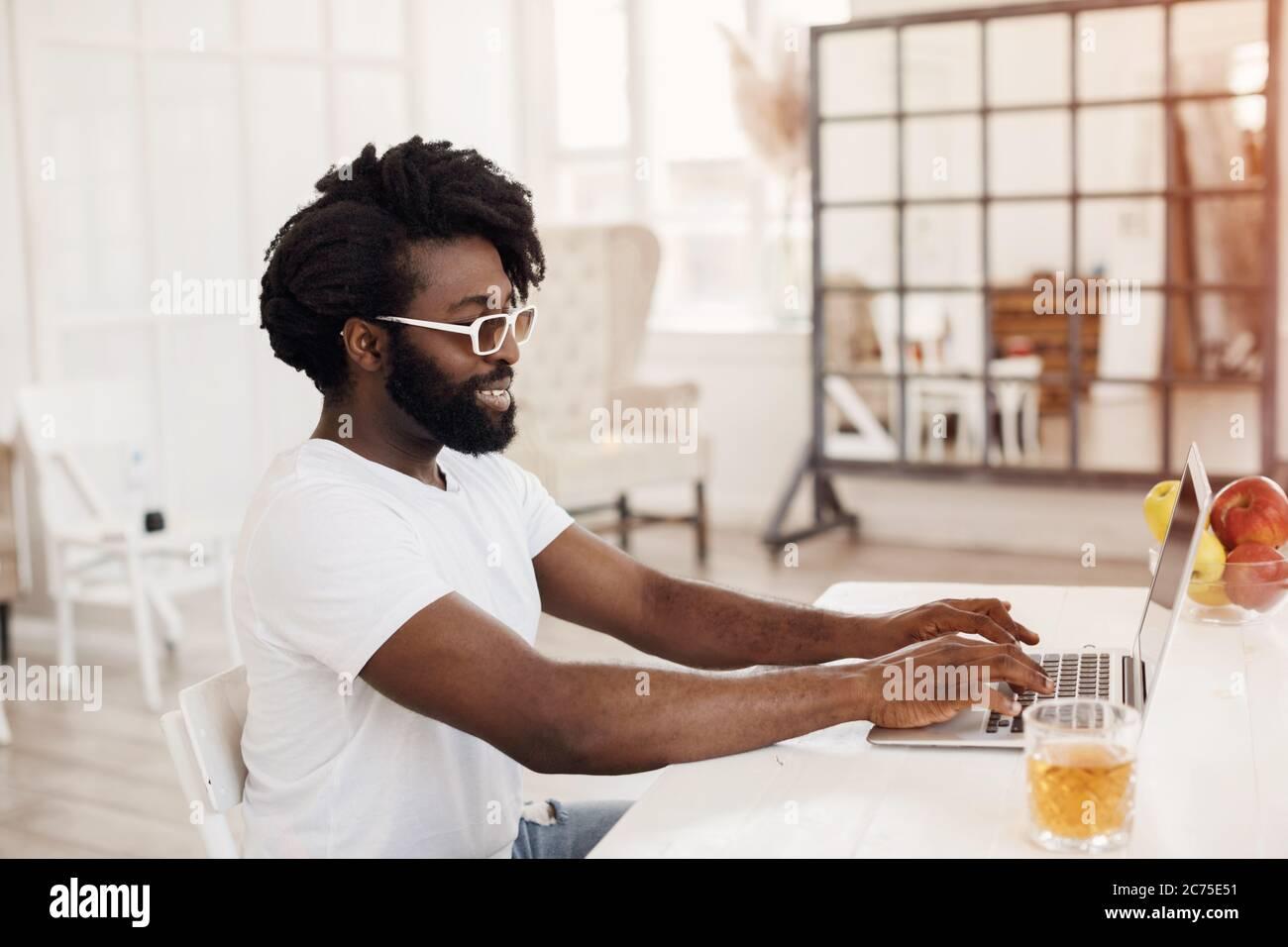 Jeune homme noir travaillant à la maison avec un ordinateur portable Banque D'Images