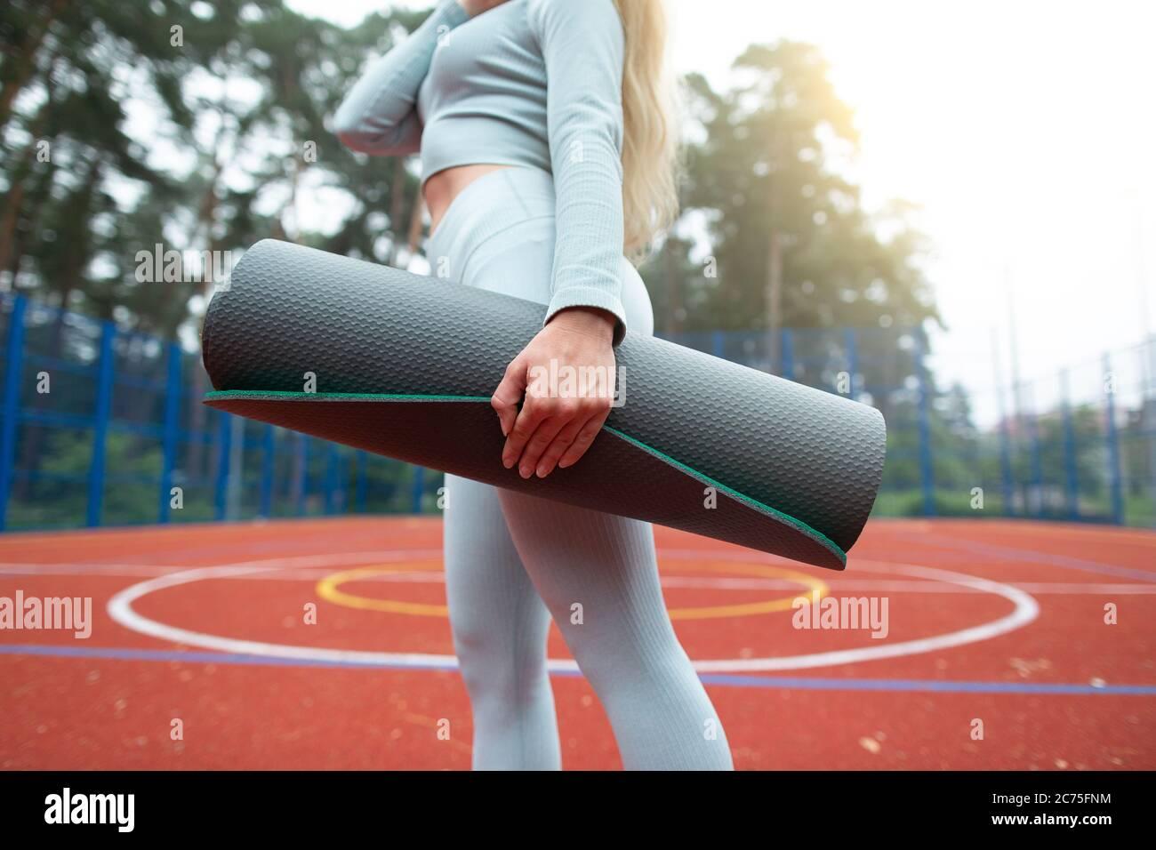 Concept de forme physique, de sport et de mode de vie sain. Image courte de jeune fille en vêtements de sport gris, tenant un tapis d'exercice et marchant à l'extérieur du sport Banque D'Images