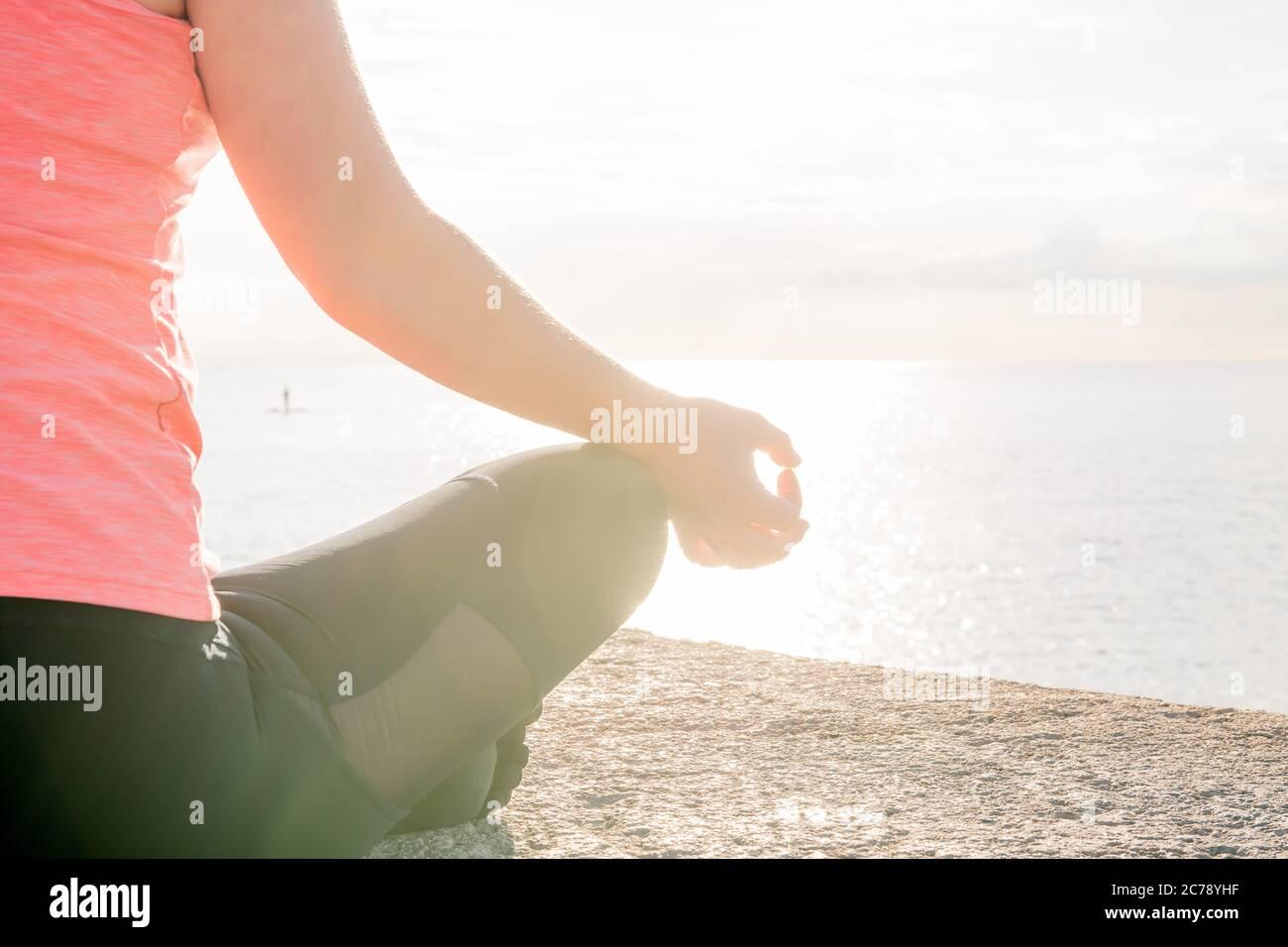 main d'une femme méconnaissable pratiquant le yoga à l'aube assise dans la position du lotus en face de la mer, concept de santé mentale et de relaxation, le Banque D'Images
