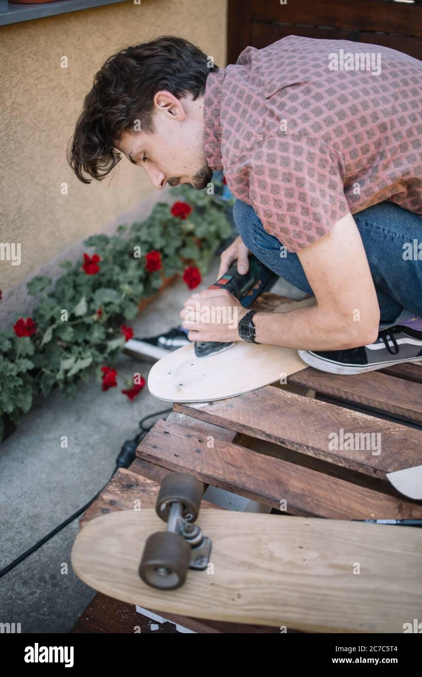 Homme concentré lissage de bois de planche à ponder Banque D'Images