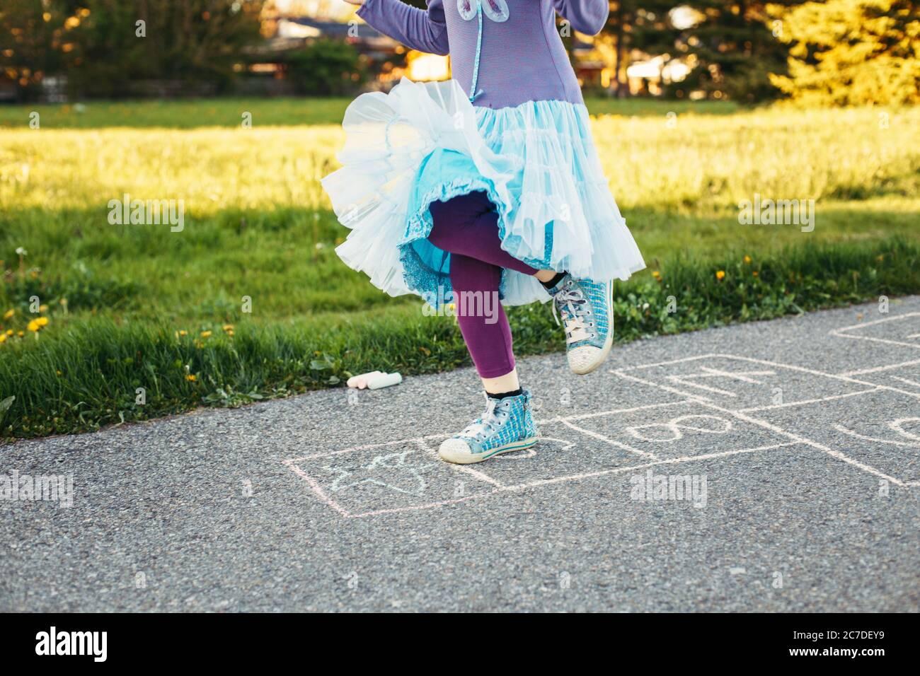 Gros plan de chld fille jouant saut de hopscotch en plein air. Jeu d'activités amusant pour les enfants sur l'aire de jeux à l'extérieur. Sports de rue de cour d'été pour les enfants. Banque D'Images