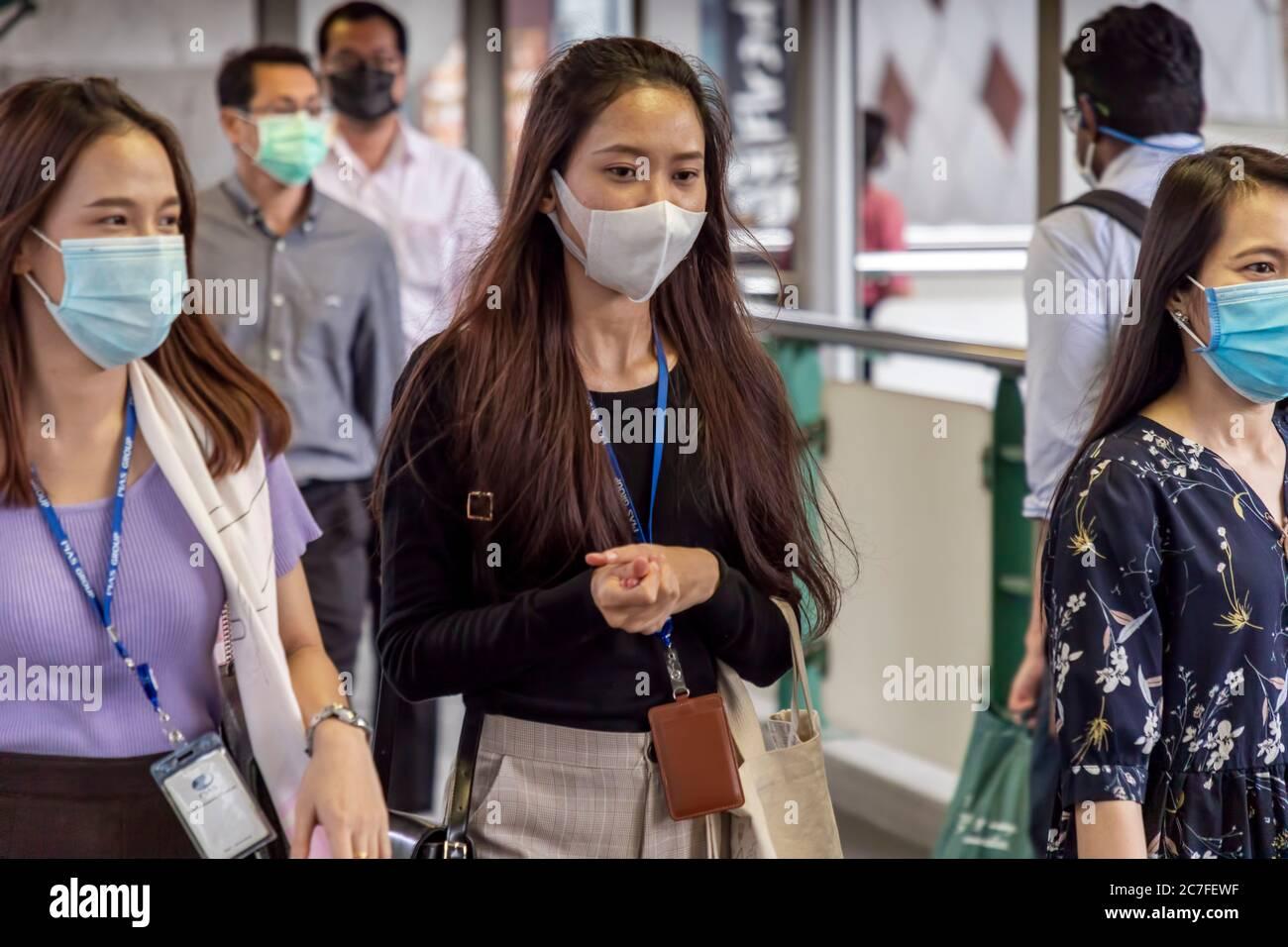 Piétons portant un masque facial marchant dans la rue pendant la pandémie de Covid 19, Bangkok, Thaïlande Banque D'Images