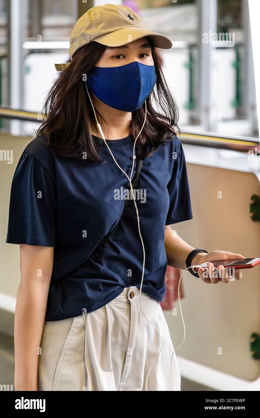 Fille portant un masque et utilisant un téléphone portable pendant la pandémie de Covid 19, Bangkok, Thaïlande Banque D'Images