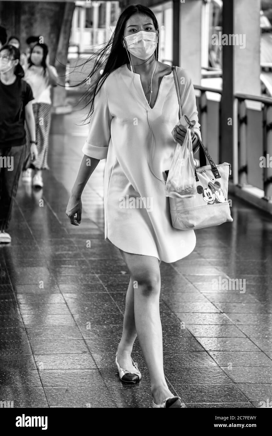 Femme portant un masque et des écouteurs marchant dans la rue pendant la pandémie de Covid 19, Bangkok, Thaïlande Banque D'Images