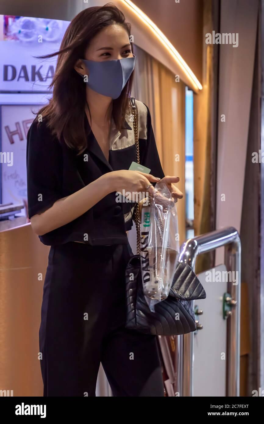 Femme portant un masque et portant un café à emporter pendant la pandémie Covid 19, Bangkok, Thaïlande Banque D'Images