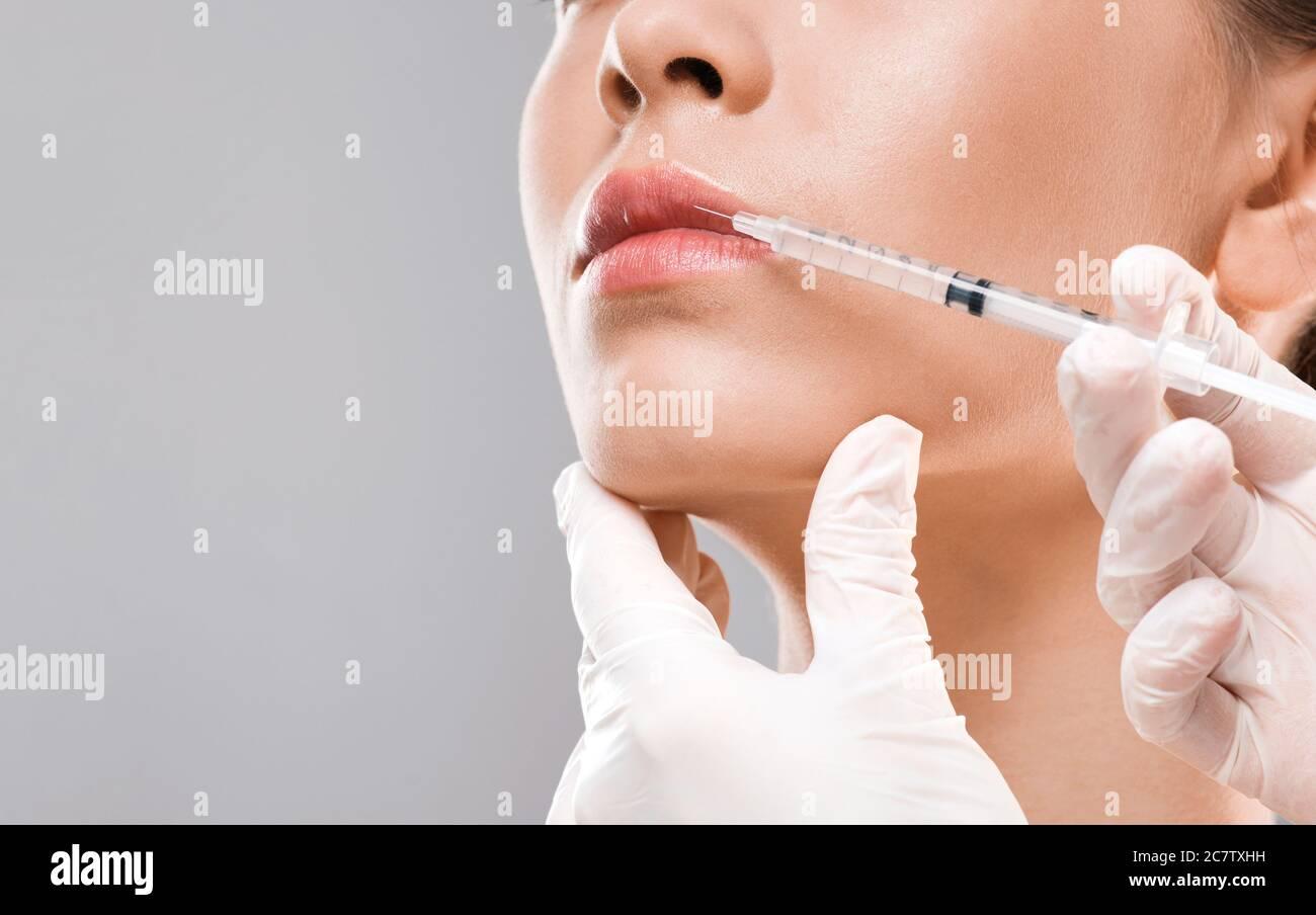 Infirmière faisant une injection de lèvre pour la jeune femme ...
