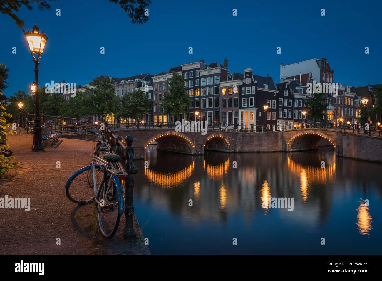 Le vélo solitaire à côté des canaux la nuit dans l'illuminé Amsterdam, pays-Bas Banque D'Images