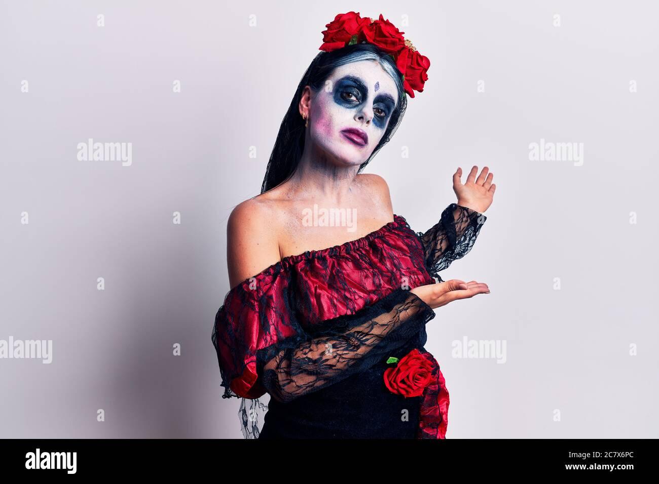 Jeune femme portant le maquillage mexicain jour de la mort invitant à entrer dans le sourire naturel avec la main ouverte Banque D'Images