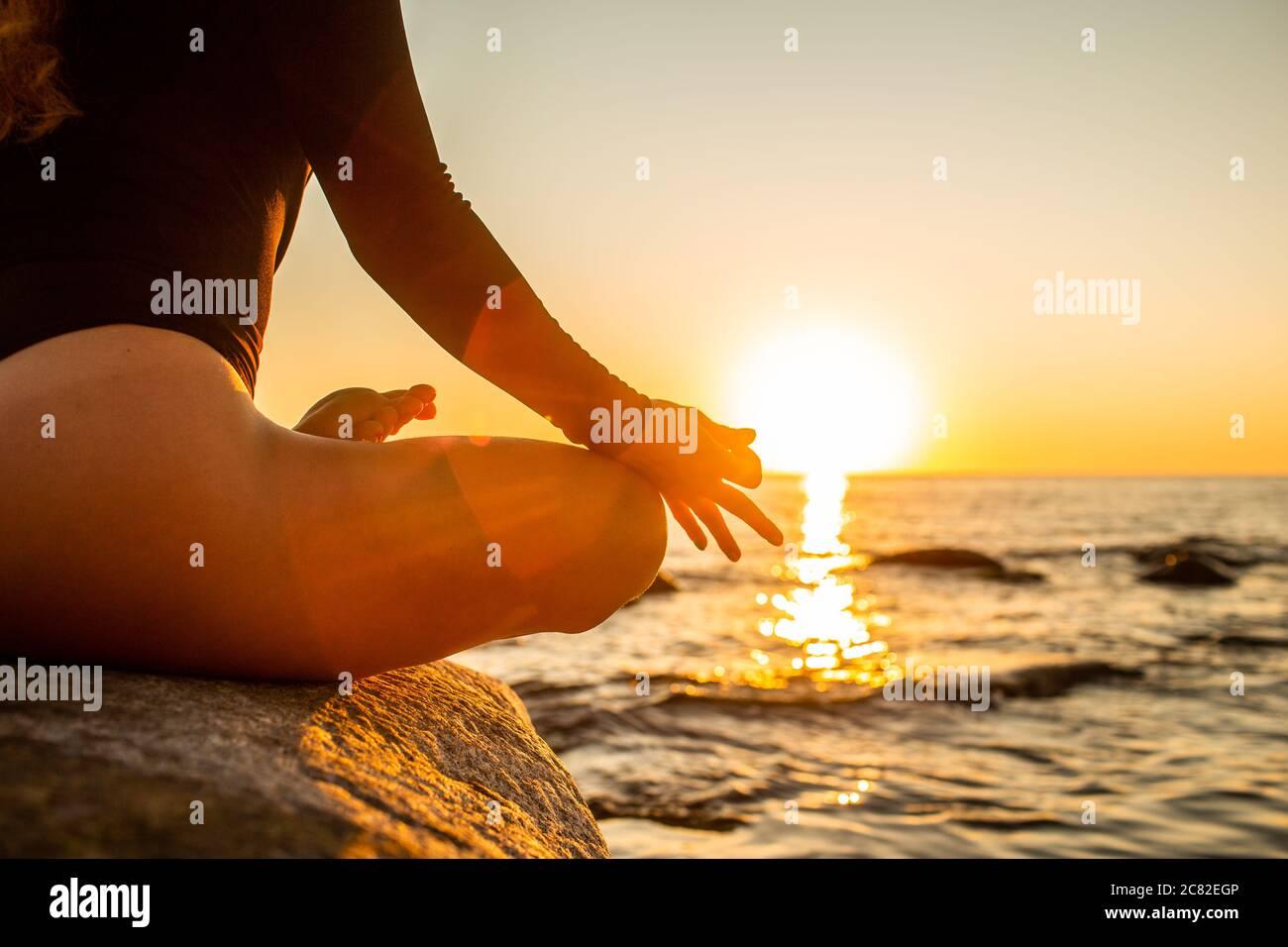 Main d'une femme méditant dans une pose de Lotus de yoga sur la plage au coucher du soleil. Fille assise sur un rocher chaud Banque D'Images