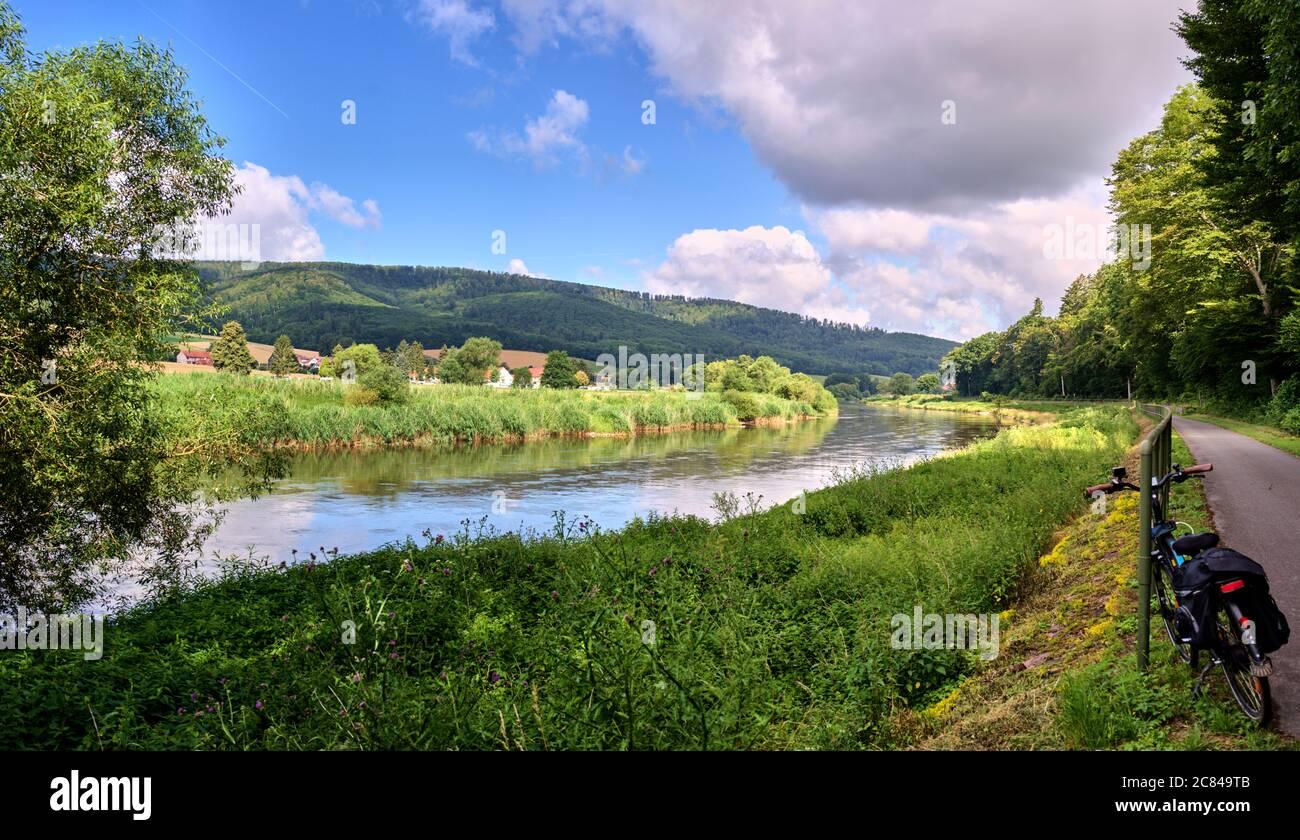 Panorama depuis le long chemin cyclable à côté du Weser en Allemagne dans le Weserbergland, avec des rives vertes et ciel nuageux Banque D'Images