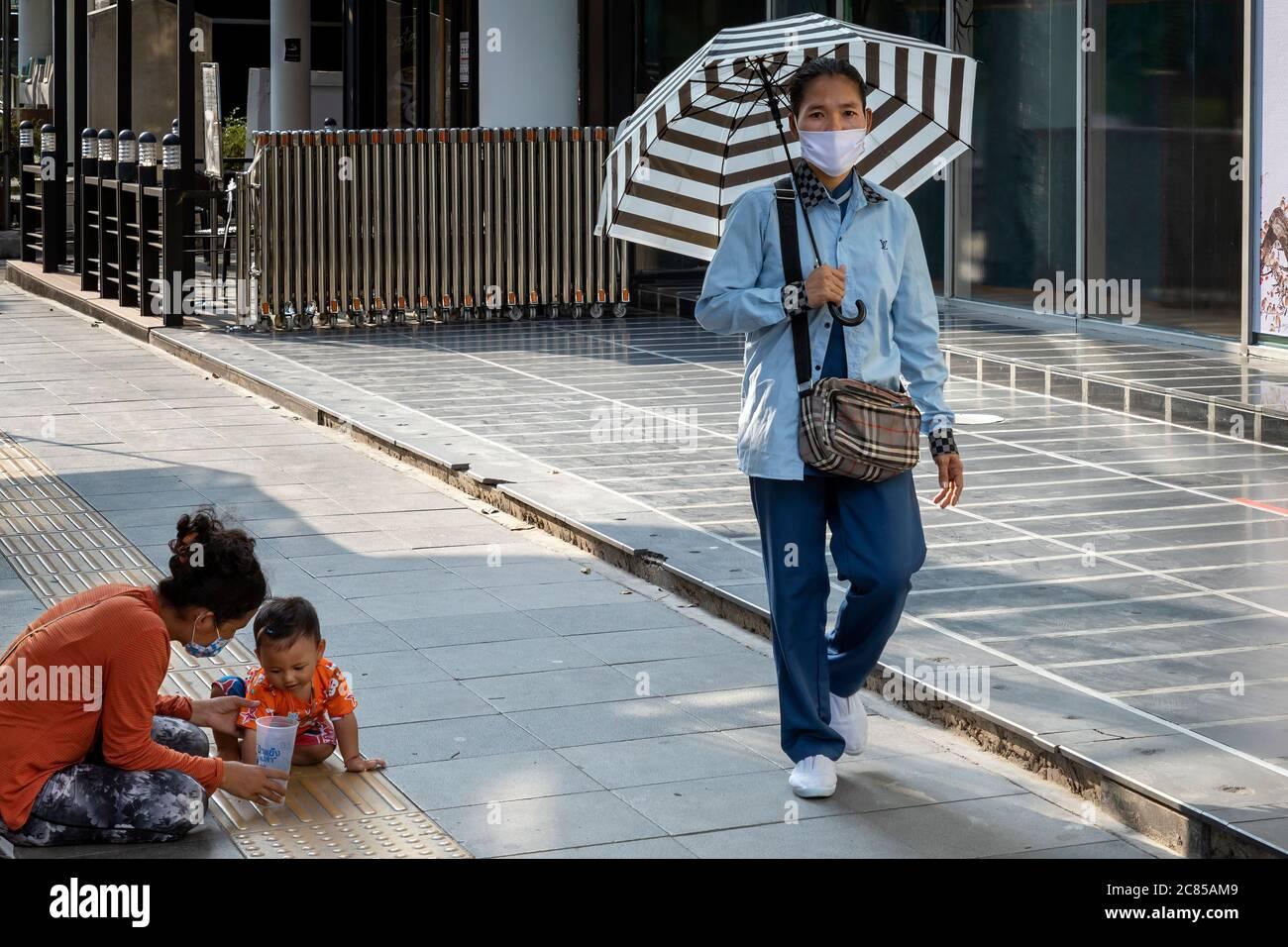 Femme portant un masque facial avec bébé mendiant dans la rue pendant la pandémie Covid 19, Bangkok, Thaïlande Banque D'Images