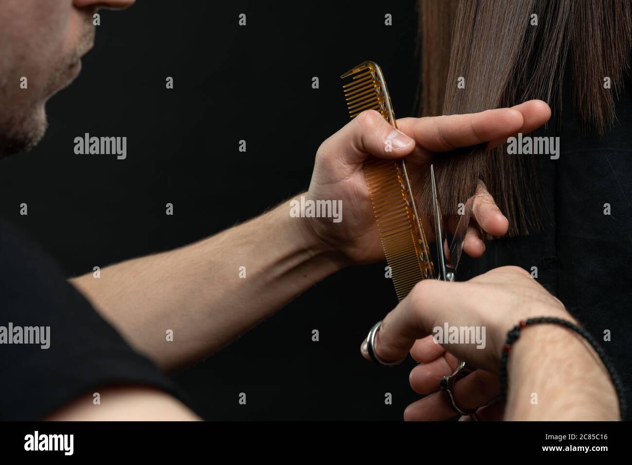 Un gros plan de coiffeur mains couper les cheveux, coiffeur avec le client Banque D'Images