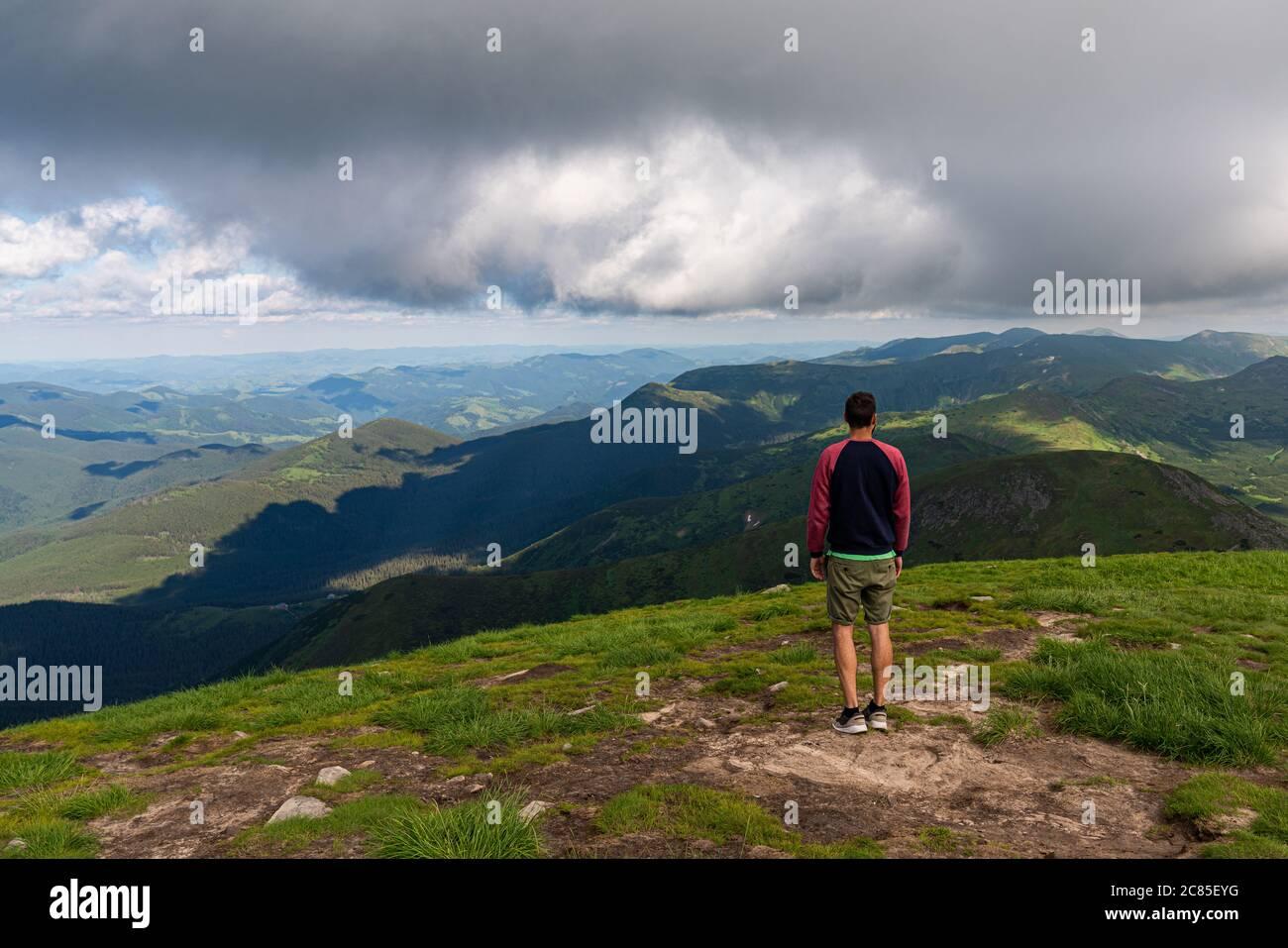 Voyageur debout sur la falaise de haute montagne, en admirant le paysage au sommet de la montagne. Vue POV. Concept de liberté de randonnée Banque D'Images