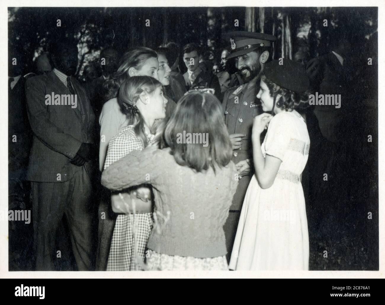 Haile Selassie I - Prince héritier et régent de l'Empire éthiopien (de 1916 à 1928), puis Roi et Régent (de 1928 à 1930), et enfin Empereur (de 1930 à 1974). Il est une figure déterminante dans l'histoire moderne de l'Éthiopie. Entouré de jeunes filles européennes lors d'une réception informelle. La photographie a été prise par le photographe de la Cour arménienne Haigaz Boyadjian Date: Vers les années 1930 Banque D'Images