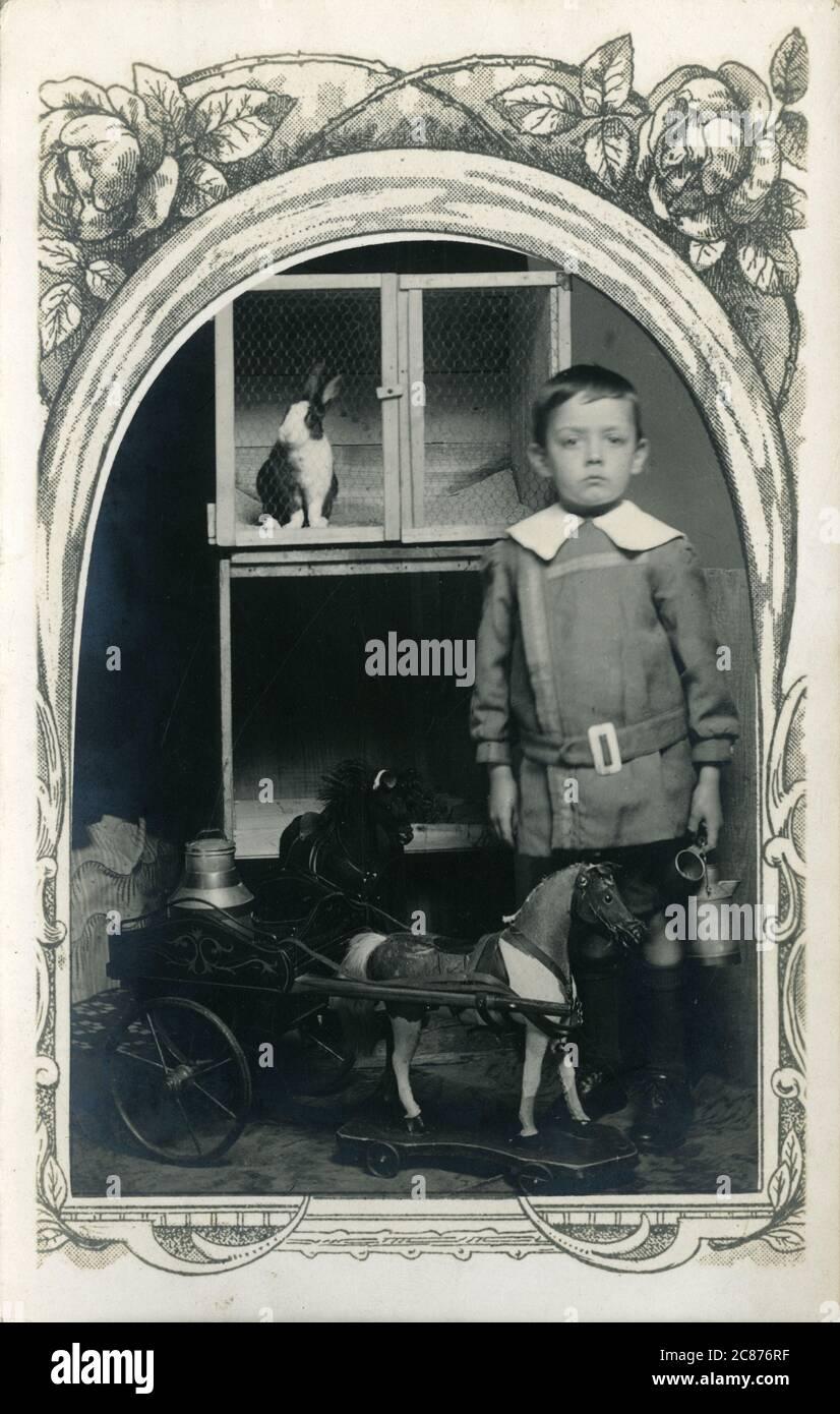 Un garçon édouardien avec un cheval et un ampli jouet ; chariot, Grande-Bretagne. Il est debout devant une huche de lapin. 1900 Banque D'Images