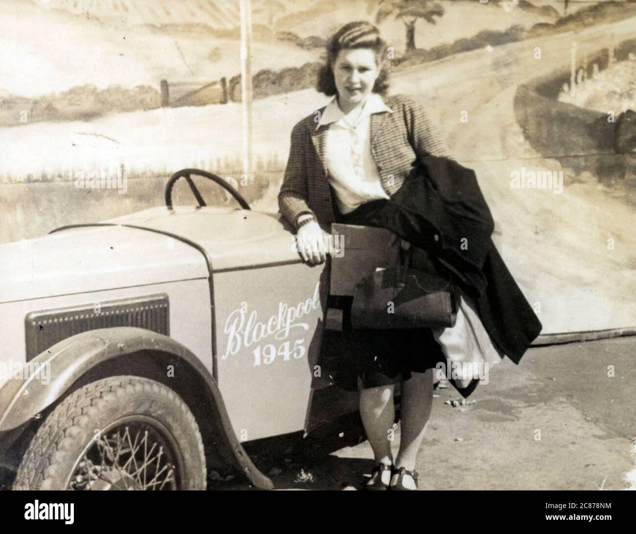 Une jeune femme sur le front de mer de Blackpool pose pour une photo « Sunny snapshots » à côté d'une petite voiture de sport « prop » devant un fond peint représentant une scène de campagne. Date: 1945 Banque D'Images