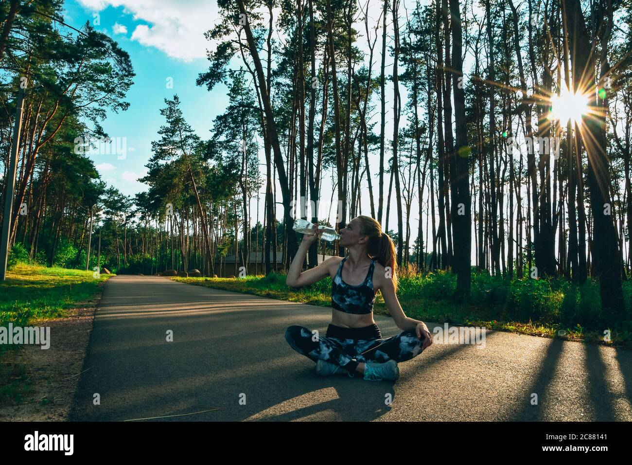 Une jeune femme boit de l'eau après avoir fait du jogging à l'extérieur en forêt. Une fille en forme saine assise dans la posture du lotus et de l'eau potable Banque D'Images