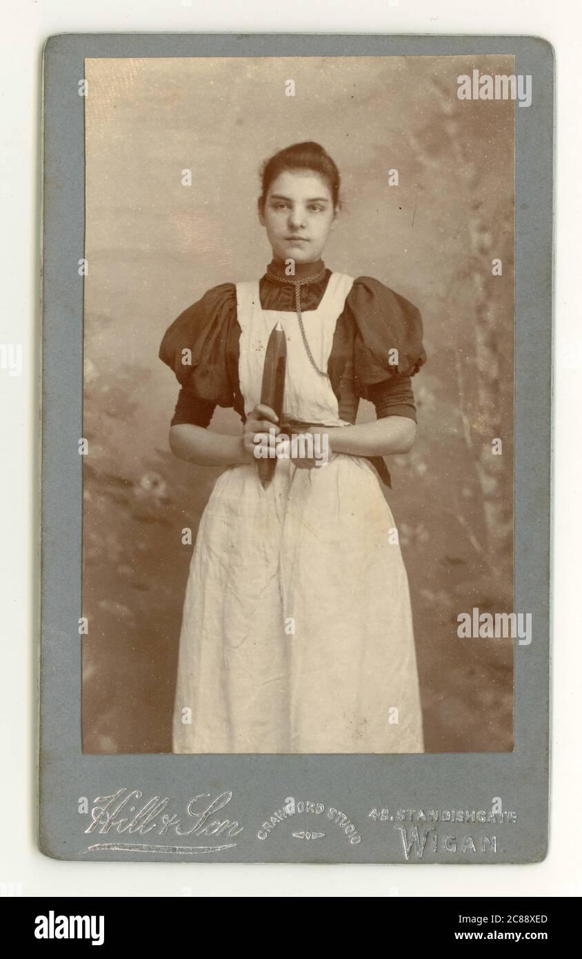 Carte de visite victorienne originale (CDV) d'une jeune fille attirante en coton, tenant une navette à rotation, Standishgate, Wigan, Lancashire, Angleterre, Royaume-Uni vers 1894 Banque D'Images