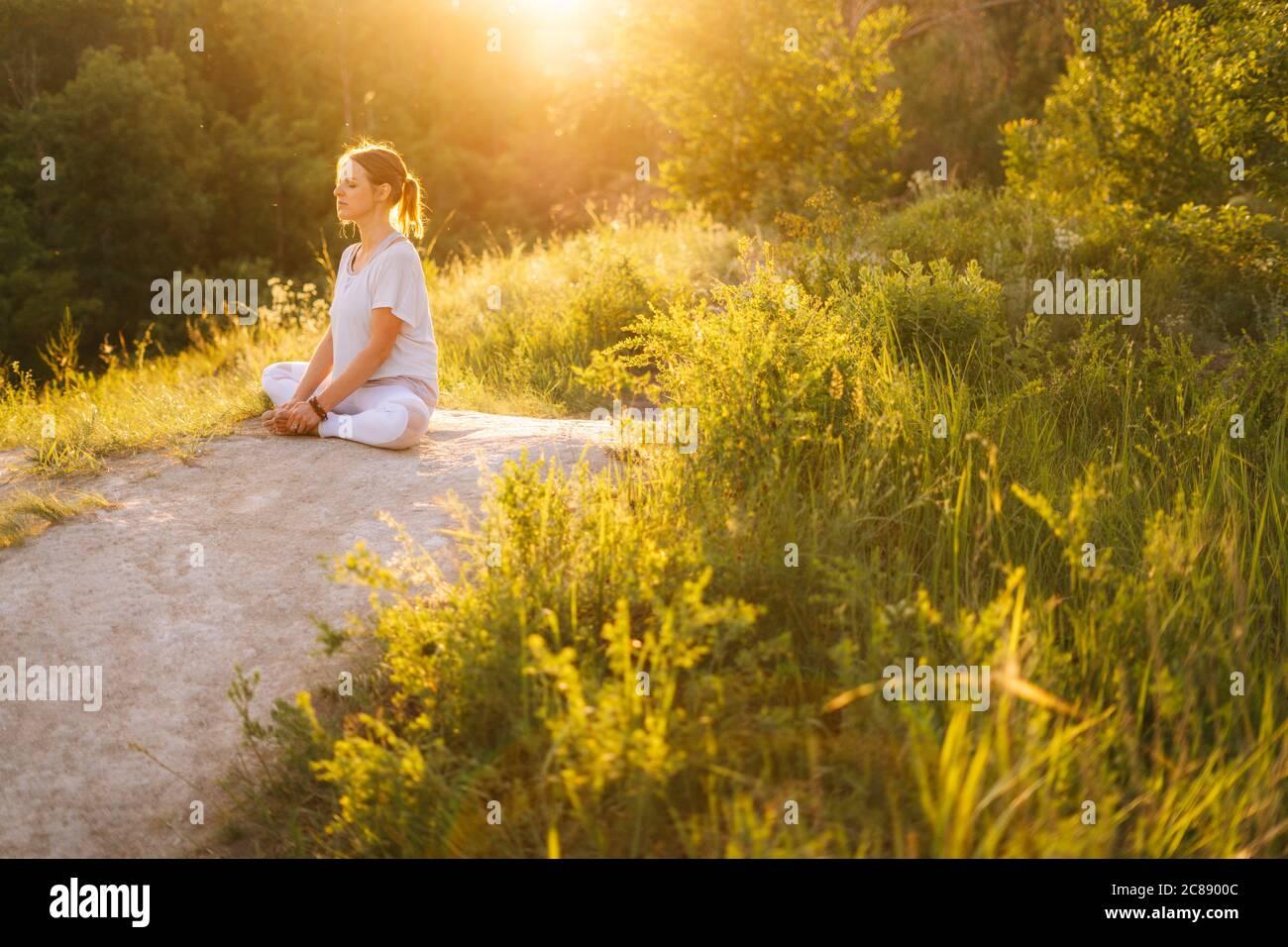 Paix et tranquillité complètes jeune femme méditant assis en position lotus avec les yeux fermés Banque D'Images