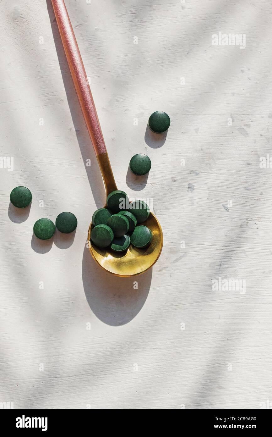 Comprimés de spiruline ou de chlorella dans une cuillère sur une table blanche Banque D'Images