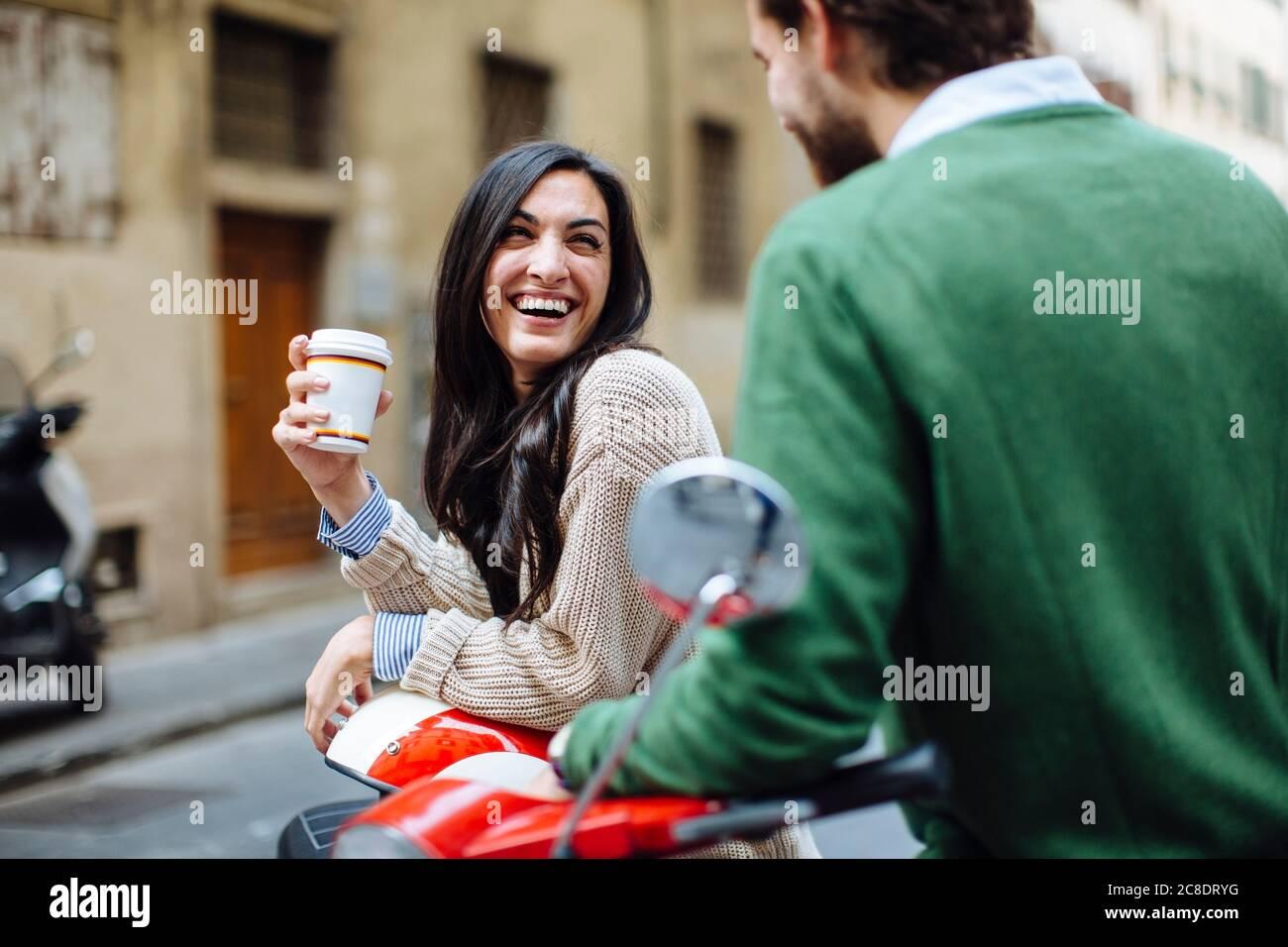 Bonne femme tenant un café en regardant le petit ami tout en s'appuyant sur Vespa Banque D'Images