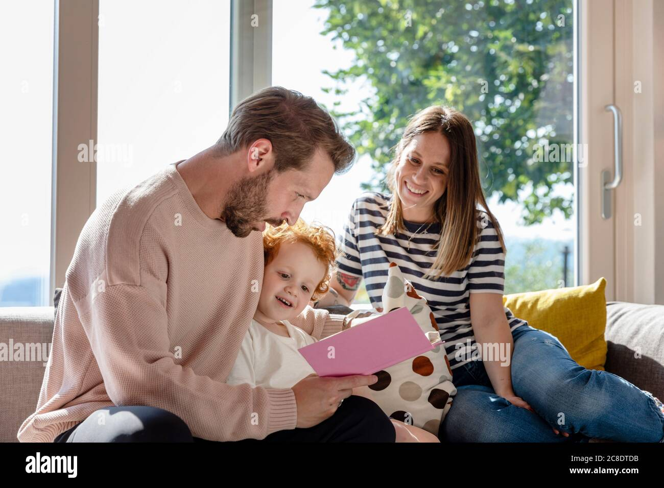 Femme souriante assise et regardant un homme lisant un livre d'images pour garçon dans la salle de séjour Banque D'Images