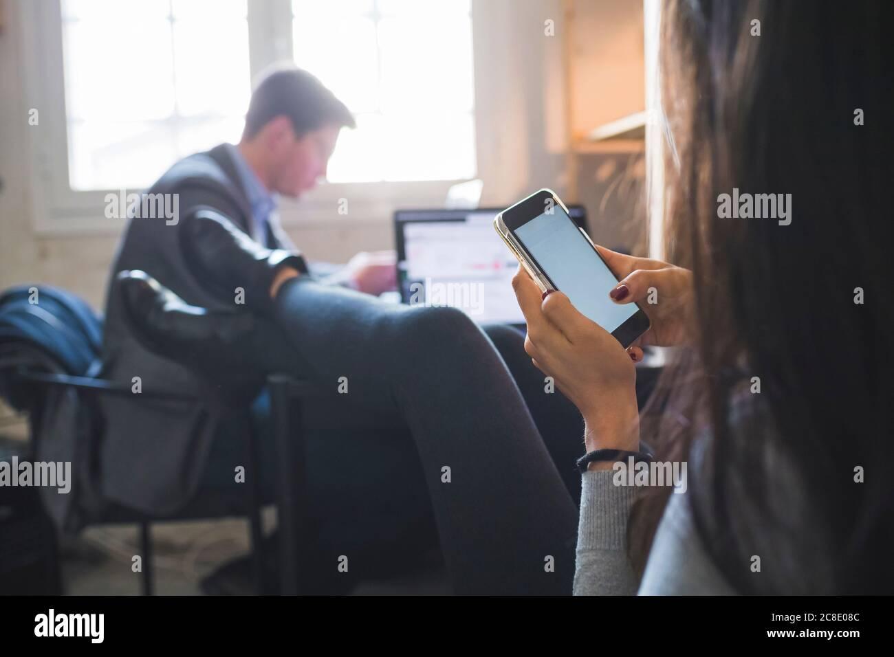 Femme détendue utilisant un smartphone au bureau avec un homme d'affaires en arrière-plan en fonctionnement Banque D'Images