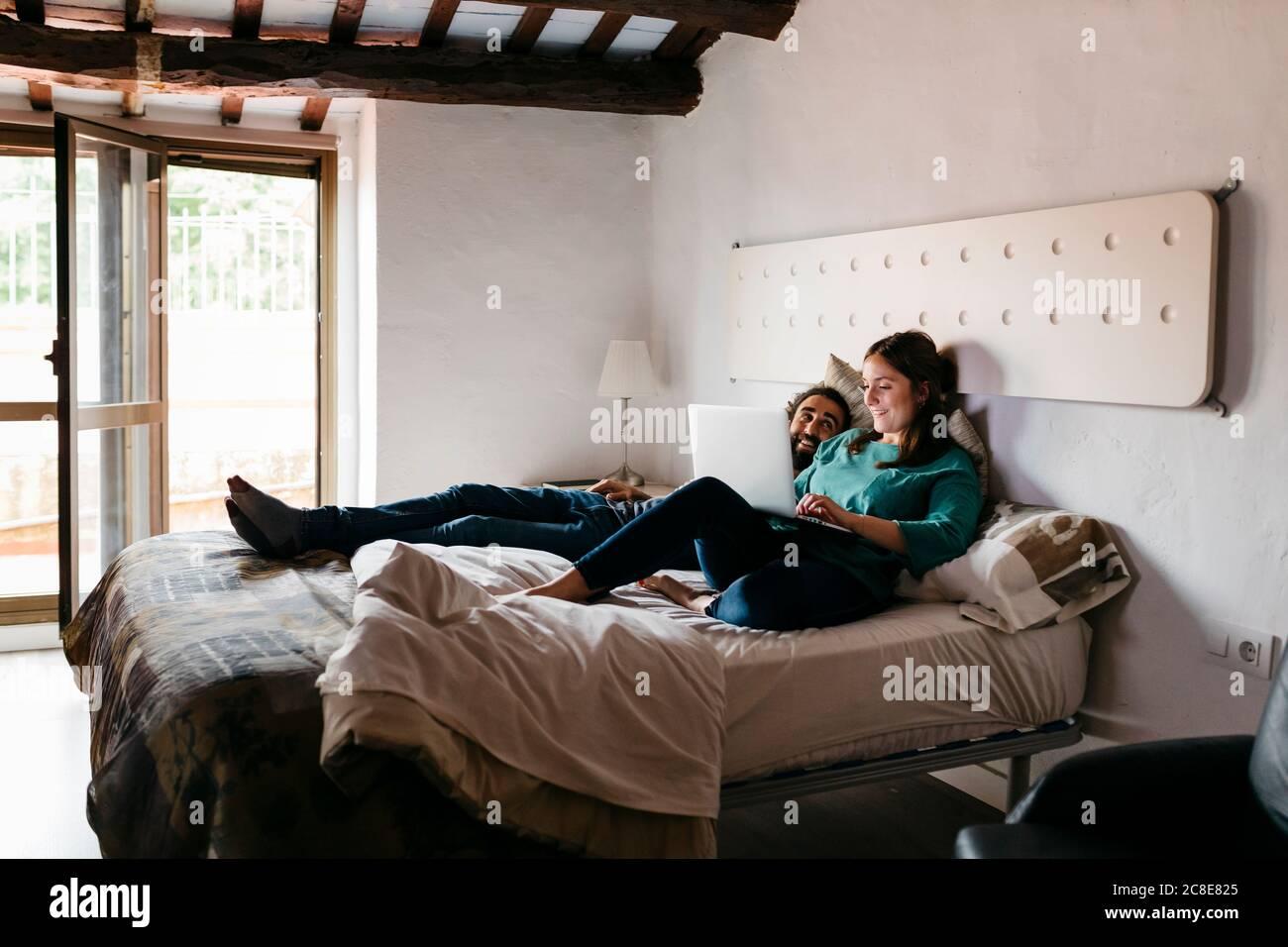 Couple regardant un film assis sur le lit à la maison Banque D'Images