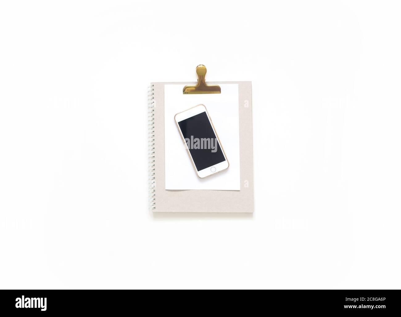 Bureau avec table et vue sur le dessus. Espace de travail avec tableau à pinces vierge, fournitures de bureau, crayon, téléphone et tasse de thé sur fond blanc. Banque D'Images