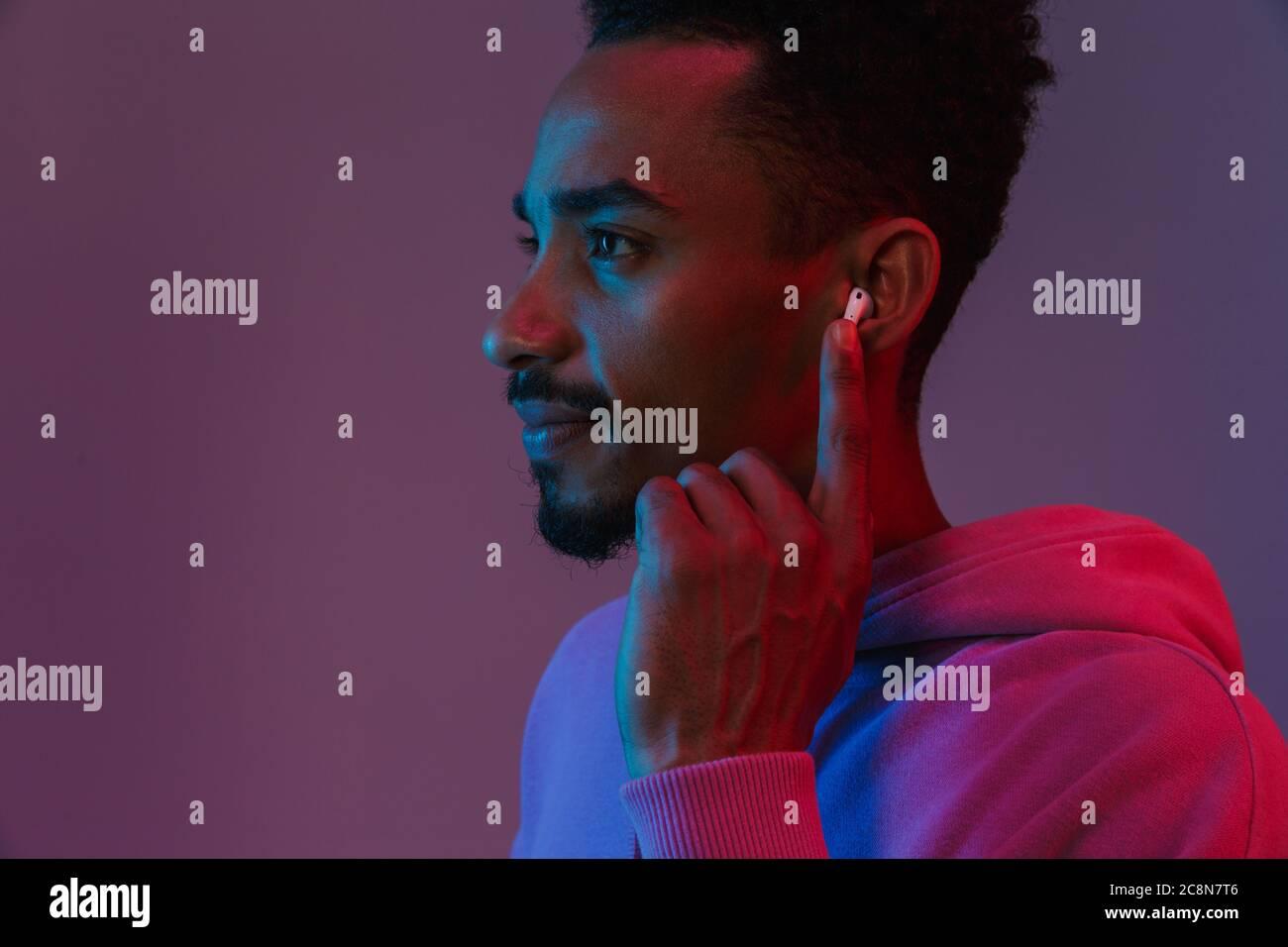 Portrait of african american man concentré en sweat coloré d'écouter de la musique avec earpod sur fond violet isolés Banque D'Images