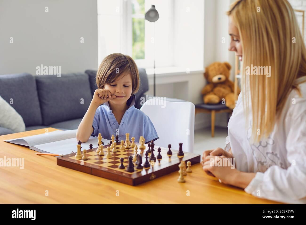Passe-temps en famille. Jeune mère jouant aux échecs avec son fils à la maison. Un petit garçon s'est engagé dans un jeu de société avec son parent dans la chambre Banque D'Images