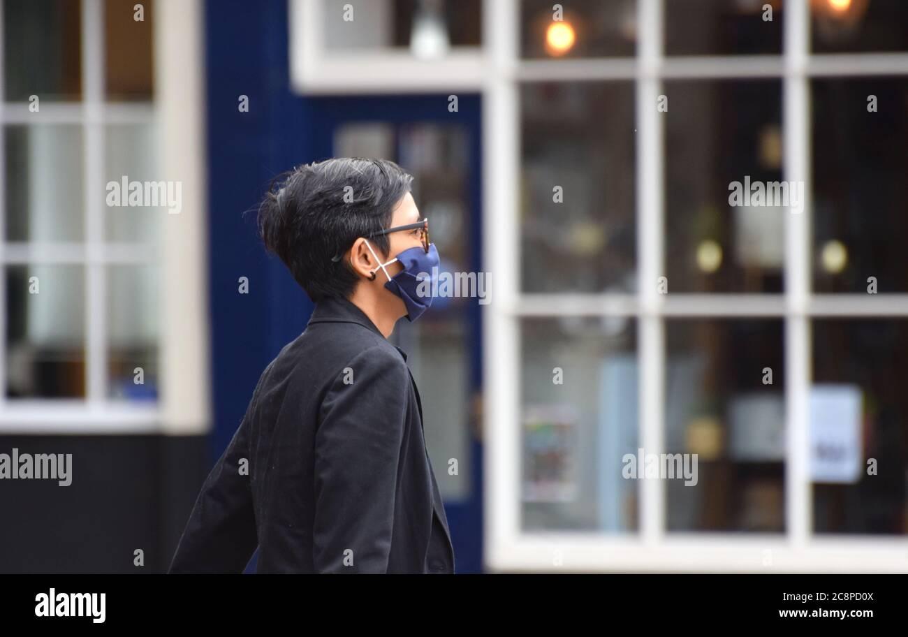 Une femme marche le long de la rue en Angleterre suite à une loi qui a été adoptée rendant le port de revêtements de visage obligatoire dans les établissements de détail le 24 2020 juillet Banque D'Images