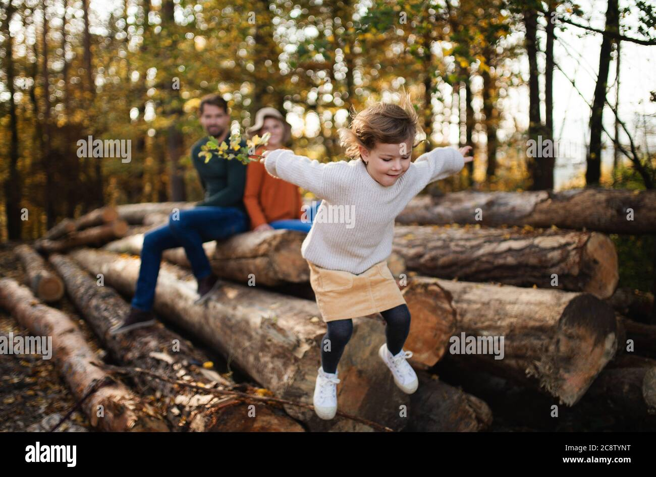 Petite fille avec des parents sur une promenade dans la forêt d'automne, saut. Banque D'Images