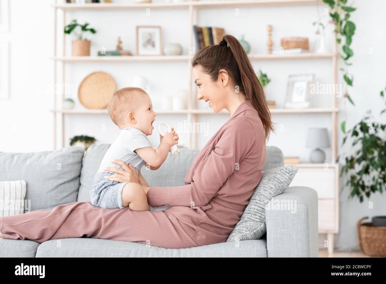 Famille heureuse et aimante. Mère et son bébé garçon jouant à la maison Banque D'Images