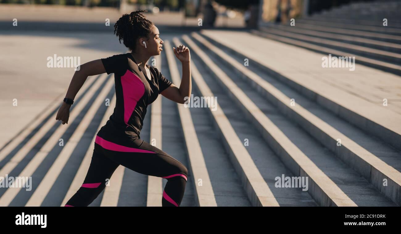 Course matinale. Une jeune fille afro-américaine avec casque sans fil et tracker de forme physique passe les escaliers Banque D'Images