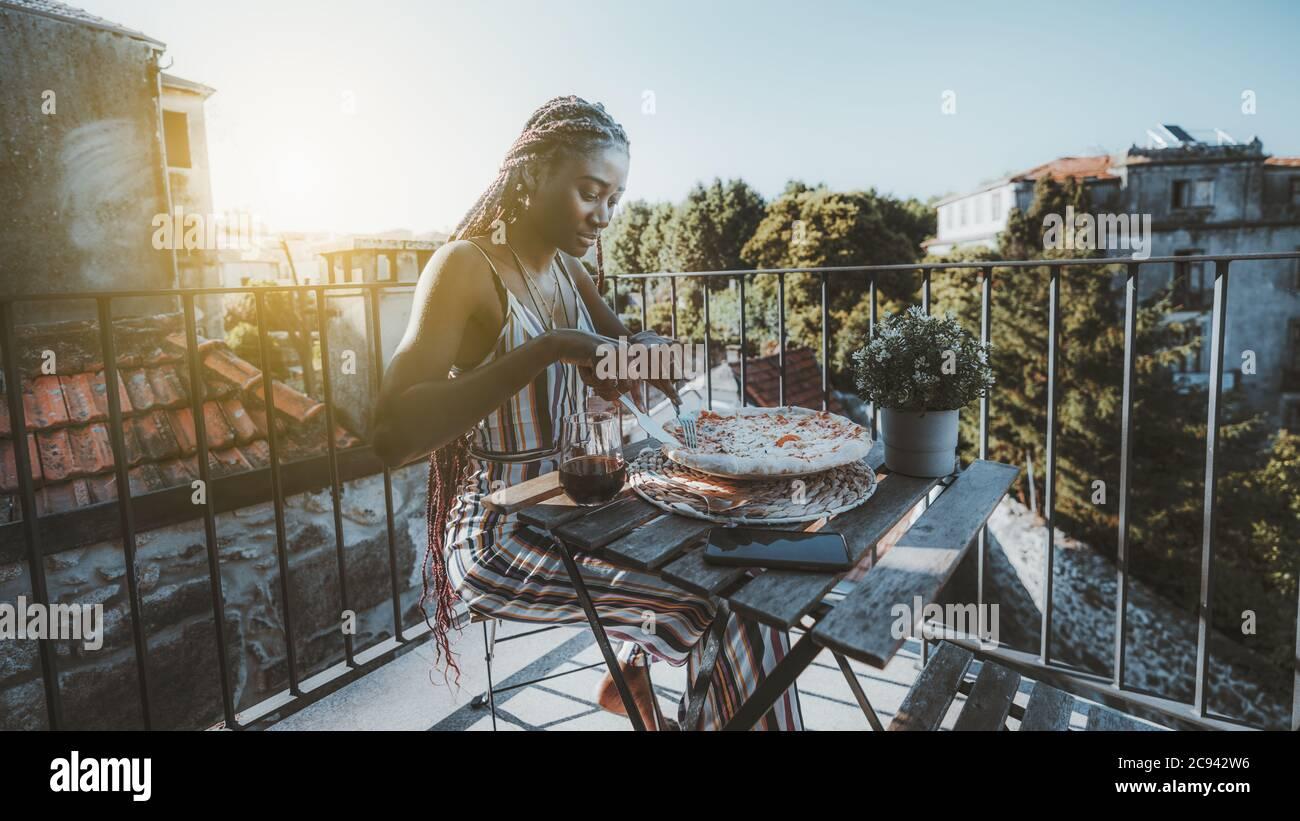 Une jeune femme noire ravishing prend le déjeuner et coupe une délicieuse pizza tout en étant assise à table avec un verre de vin Banque D'Images