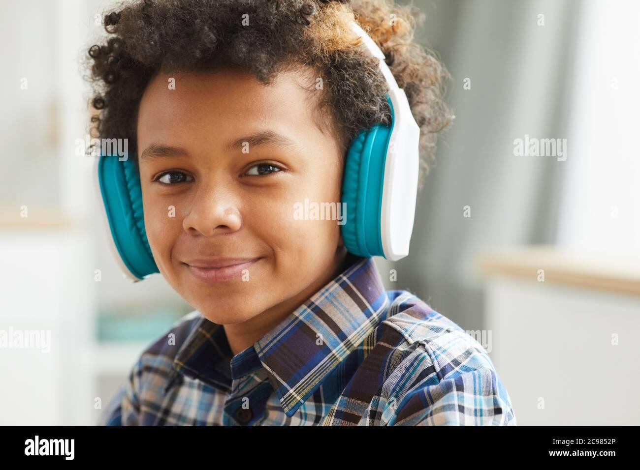 Portrait d'un petit garçon africain dans un casque souriant à l'appareil photo tout en étant assis à la maison Banque D'Images