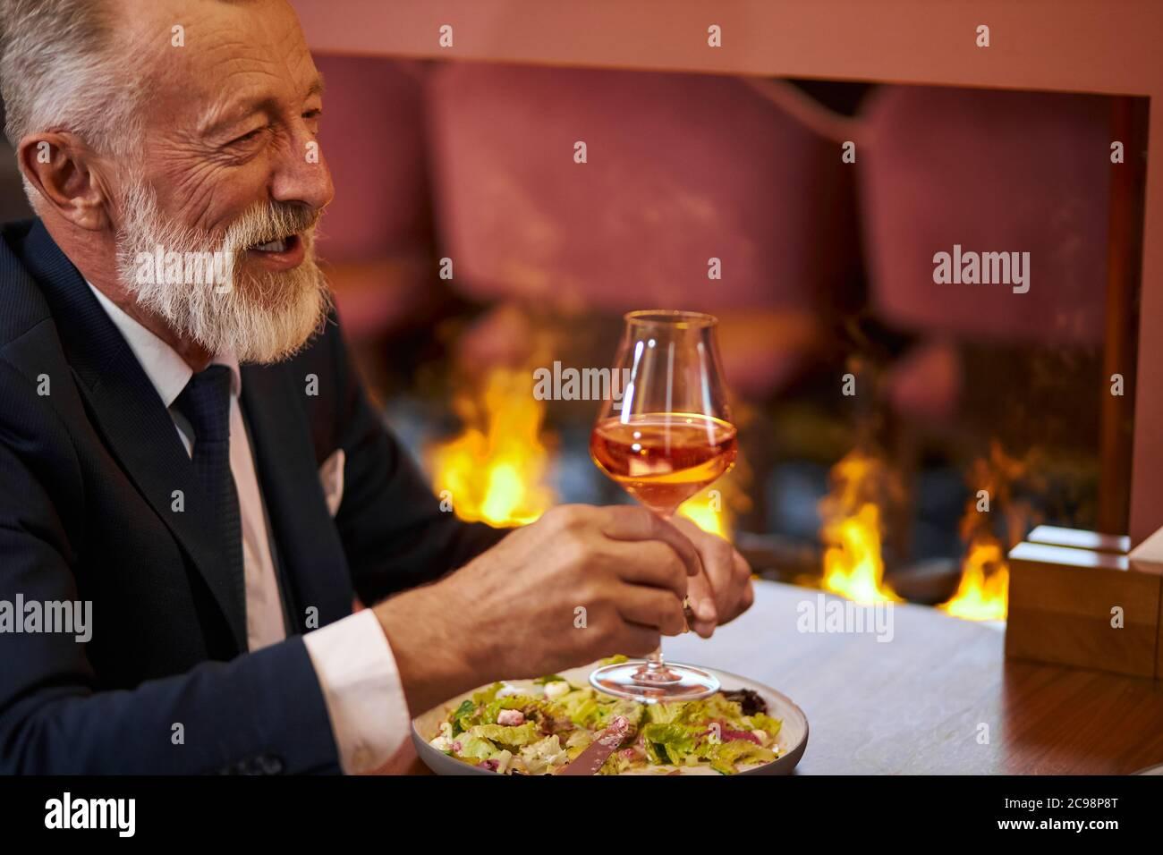 Homme à la barbe et aux cheveux gris en smoking avec verre de champagne, assis au restaurant et rire, regardez la personne en face. Contexte firemplacer Banque D'Images