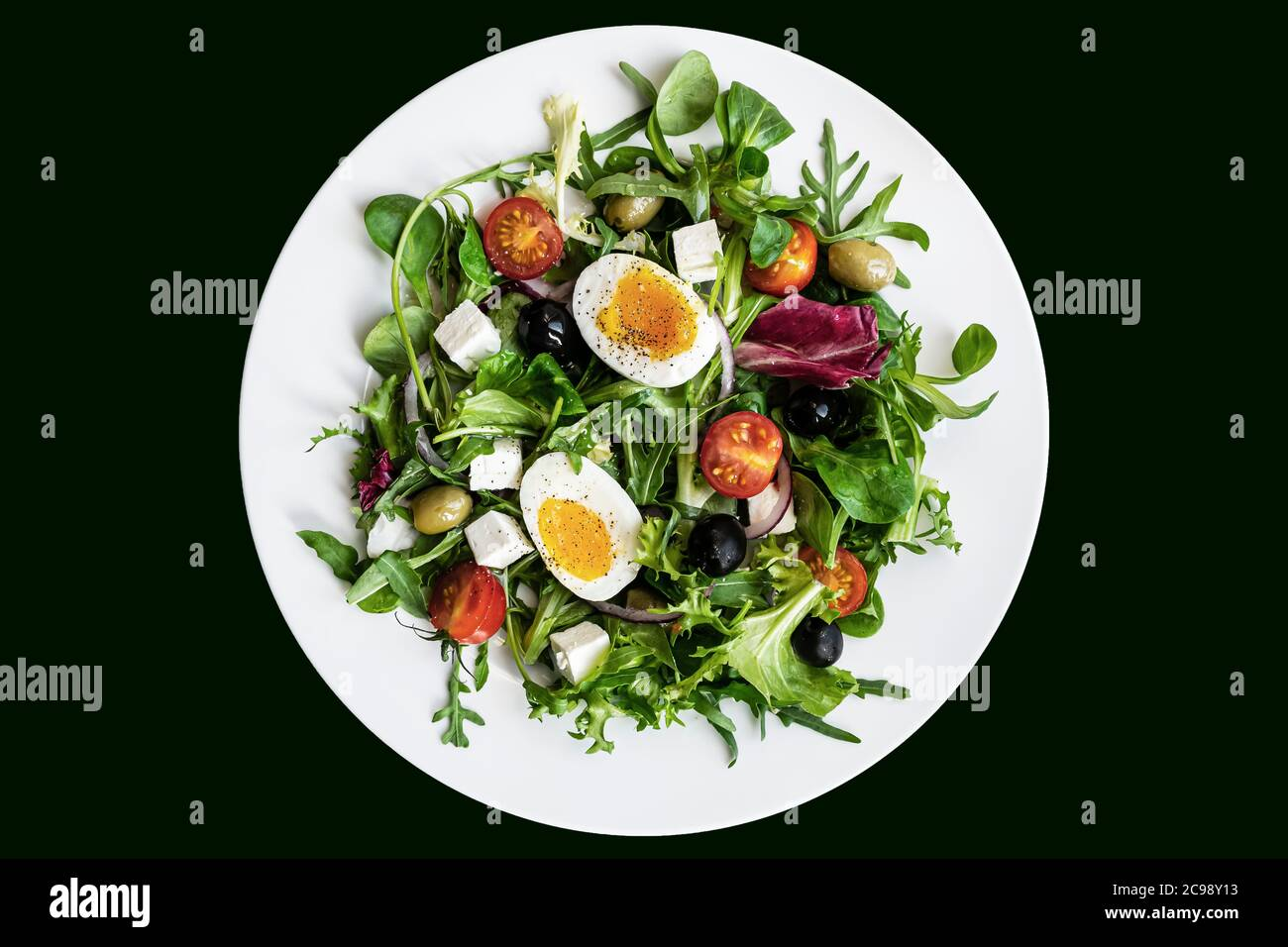 Salade verte saine avec œuf dur, feta, olives, tomates cerises dans une assiette blanche sur fond noir. Flat lay, vue de dessus Banque D'Images