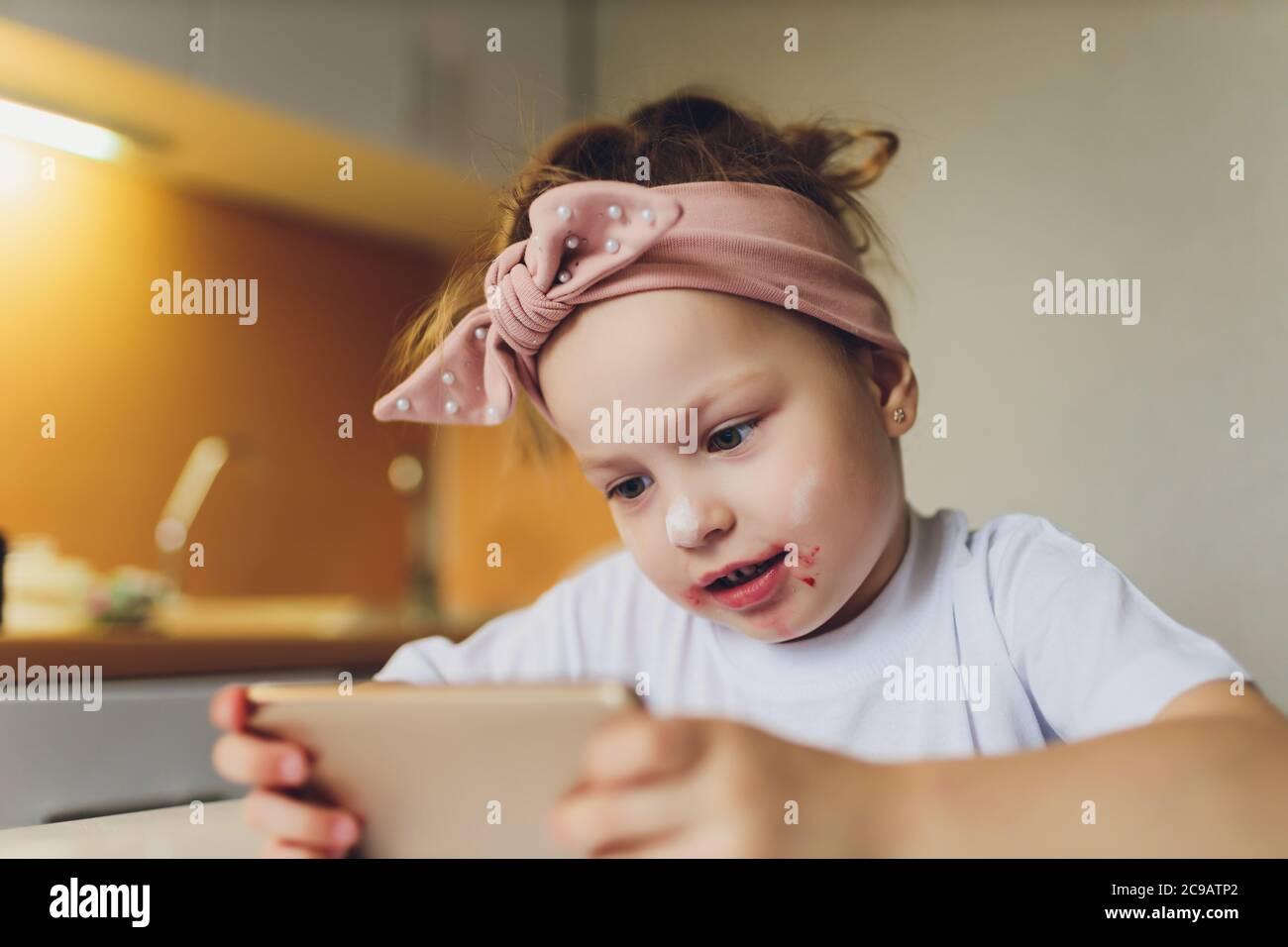 Fille mangeant à la table jouant au téléphone. Banque D'Images