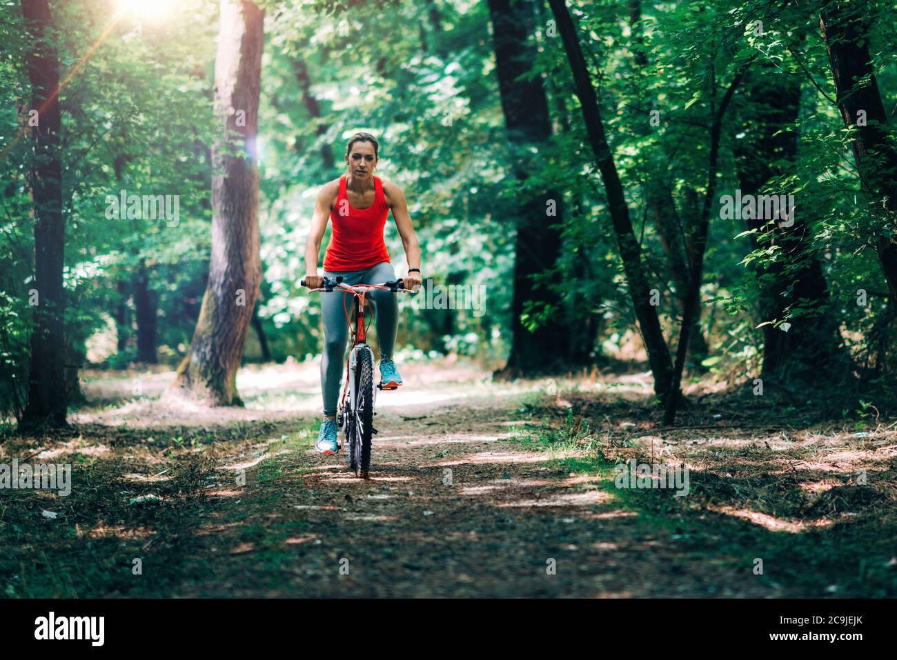 Femme à vélo dans le parc. Banque D'Images