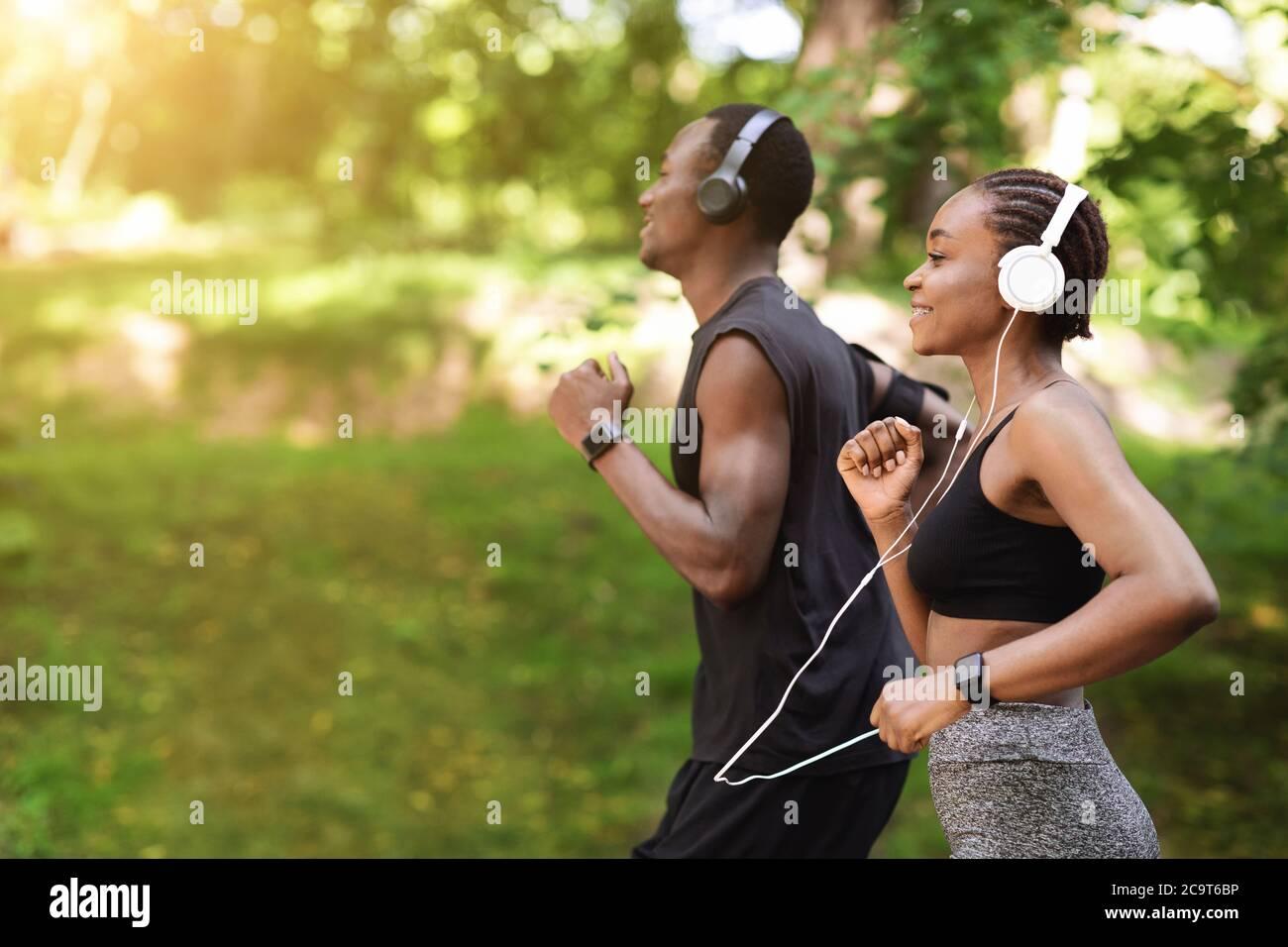 Concept de course matinale. Black sportif Homme et Femme jogging en plein air dans le parc Banque D'Images