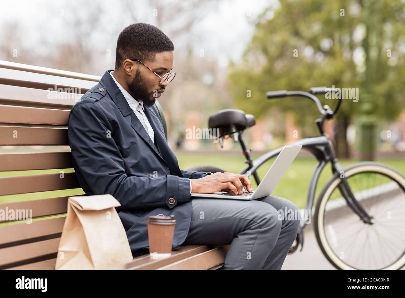 Beau directeur travaillant sur ordinateur portable dans le parc au printemps Banque D'Images