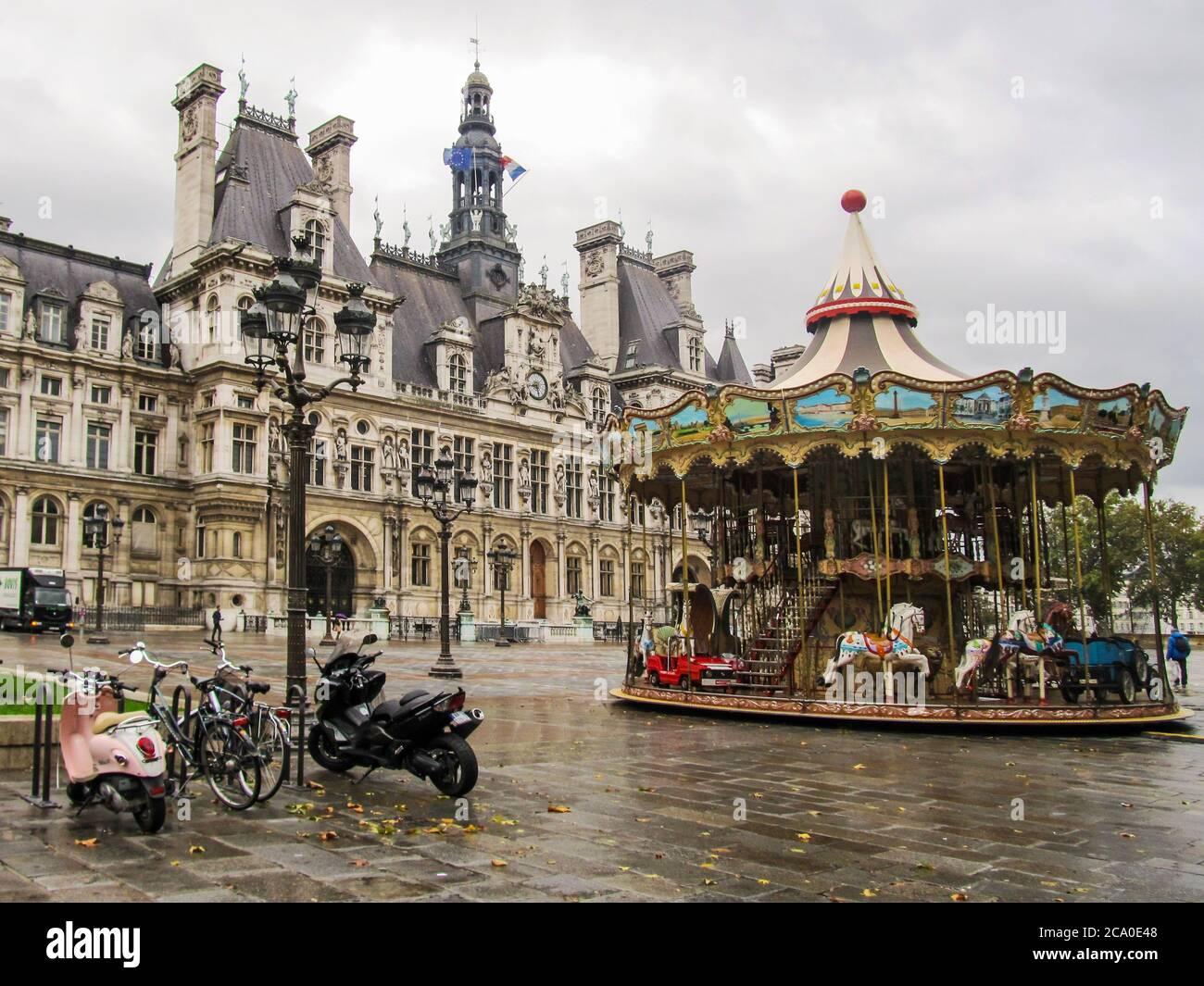 Un carrousel en face de l'Hôtel de ville, l'hôtel de ville de Paris, photographié tôt le matin lors d'un jour de pluie à Paris, France Banque D'Images