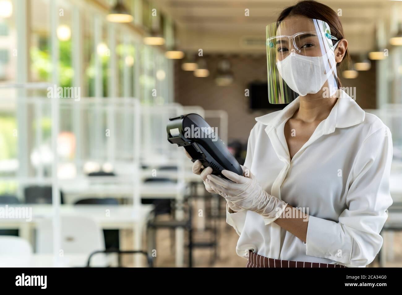 Portrait attirante serveuse asiatique porter masque et masque facial tenir le lecteur de carte de crédit pour le paiement sans contact avec fond de restaurant intérieur. Banque D'Images