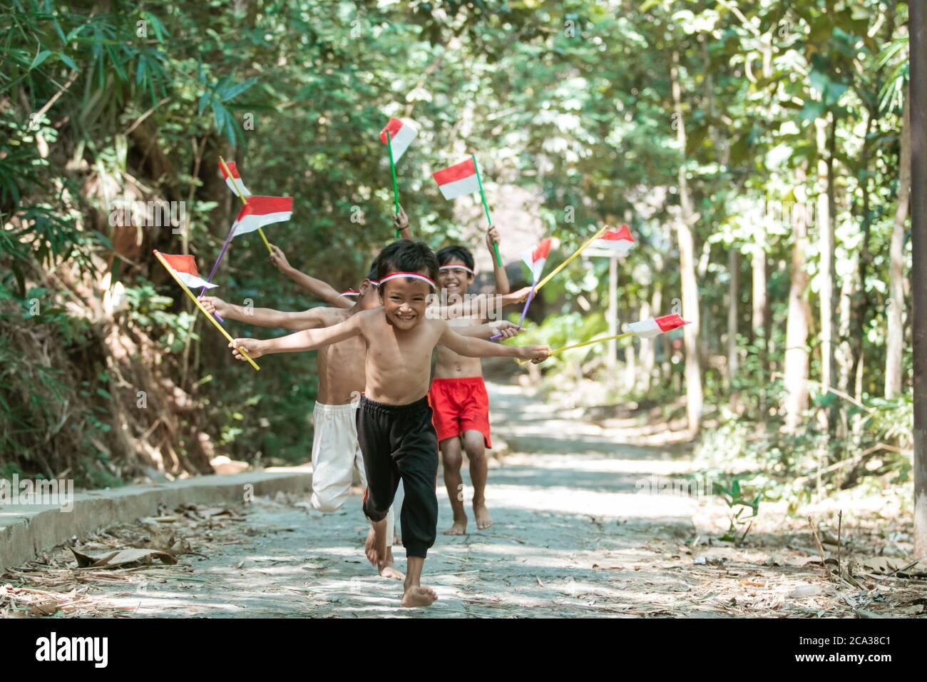 avoir un groupe amusant d'enfants courir sans vêtements pourchassant chacun autre lorsque vous tenez le petit drapeau rouge et blanc et a soulevé le drapeau sur un fond d'arbre Banque D'Images