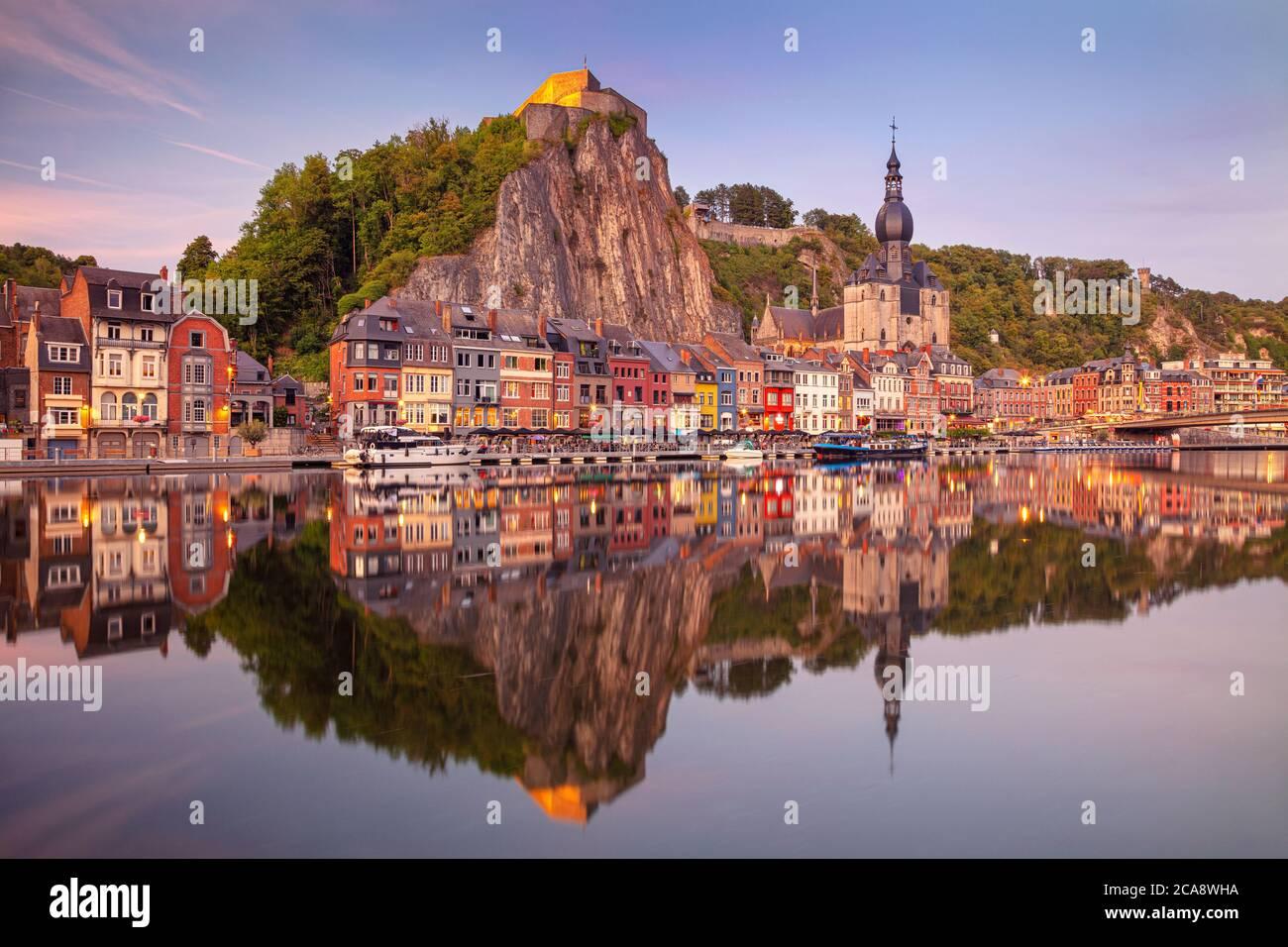 Dinant, Belgique. Image de paysage urbain de la belle ville historique de Dinant avec le reflet de la ville dans la Meuse au coucher du soleil d'été. Banque D'Images