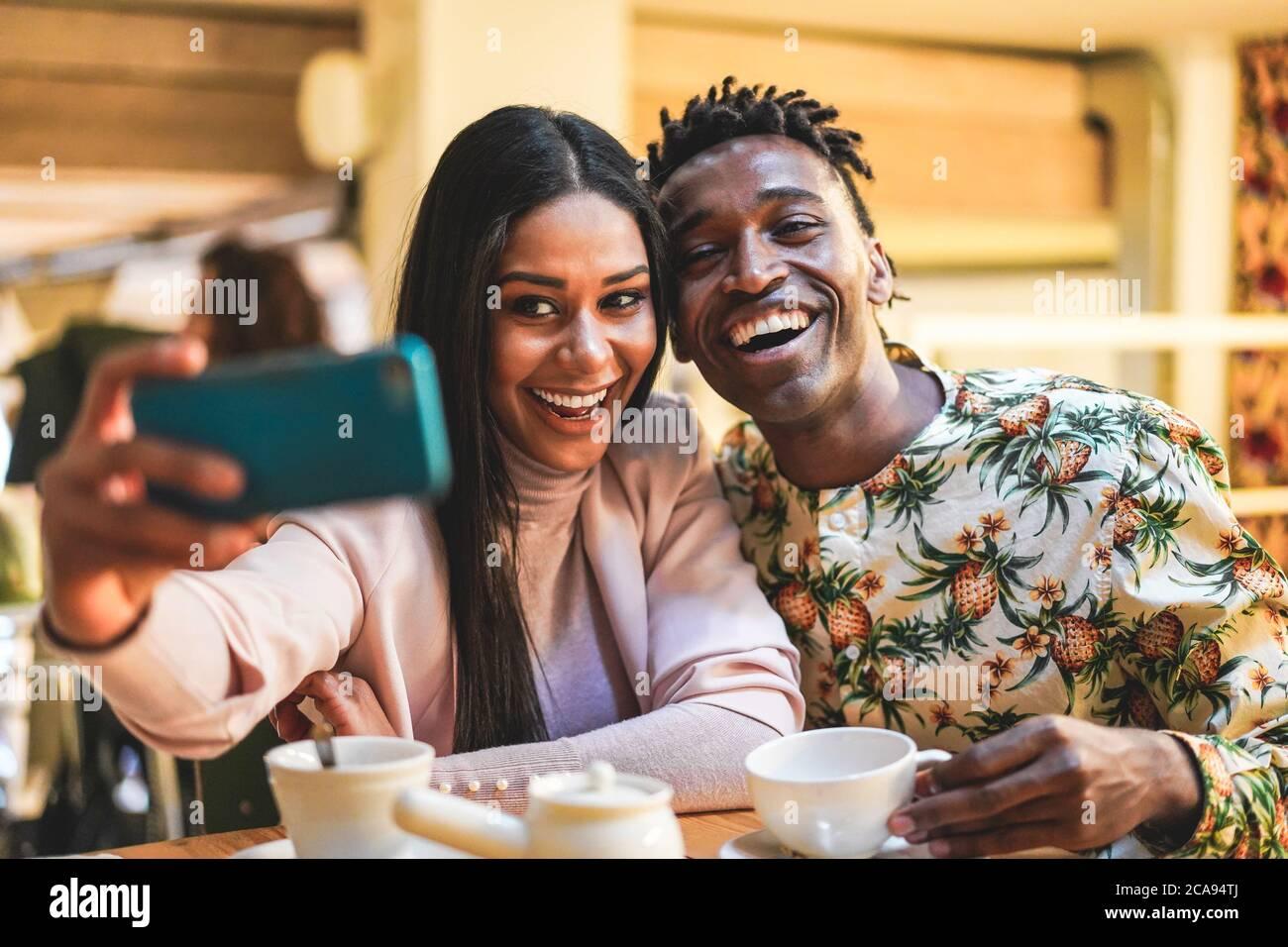 Heureux couple noir de boire du café dans la boulangerie tout en prenant selfie avec le téléphone mobile - jeunes s'amuser avec les tendances de la technologie - médias sociaux Banque D'Images