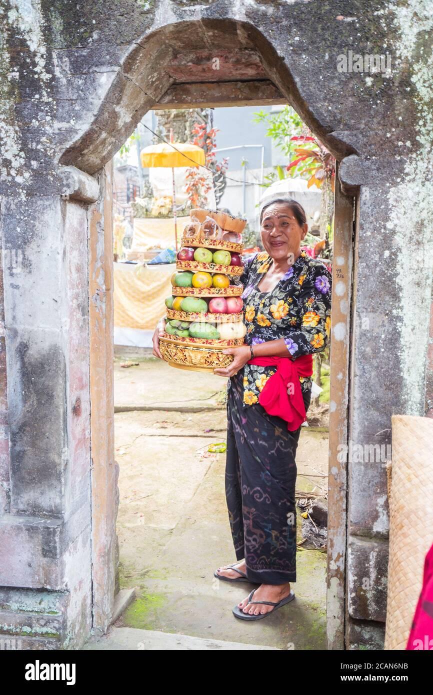 Bali / Indonésie - 15 août 2018 : Portrait d'une femme bouddhiste souriant à la porte d'un petit temple local tenant des fruits comme offrande religieuse Banque D'Images